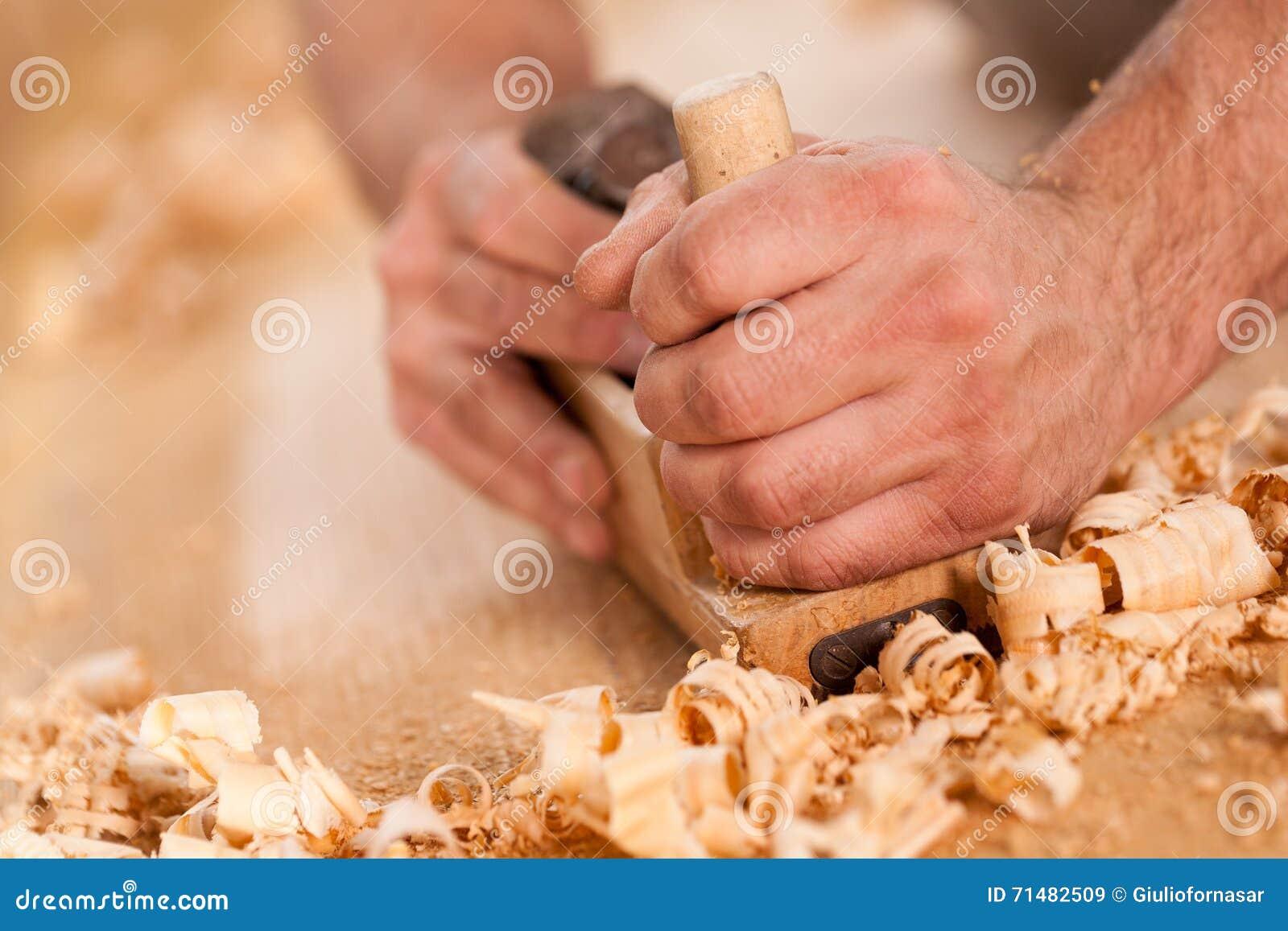 Inredningssnickarehänder som rakar med en nivå