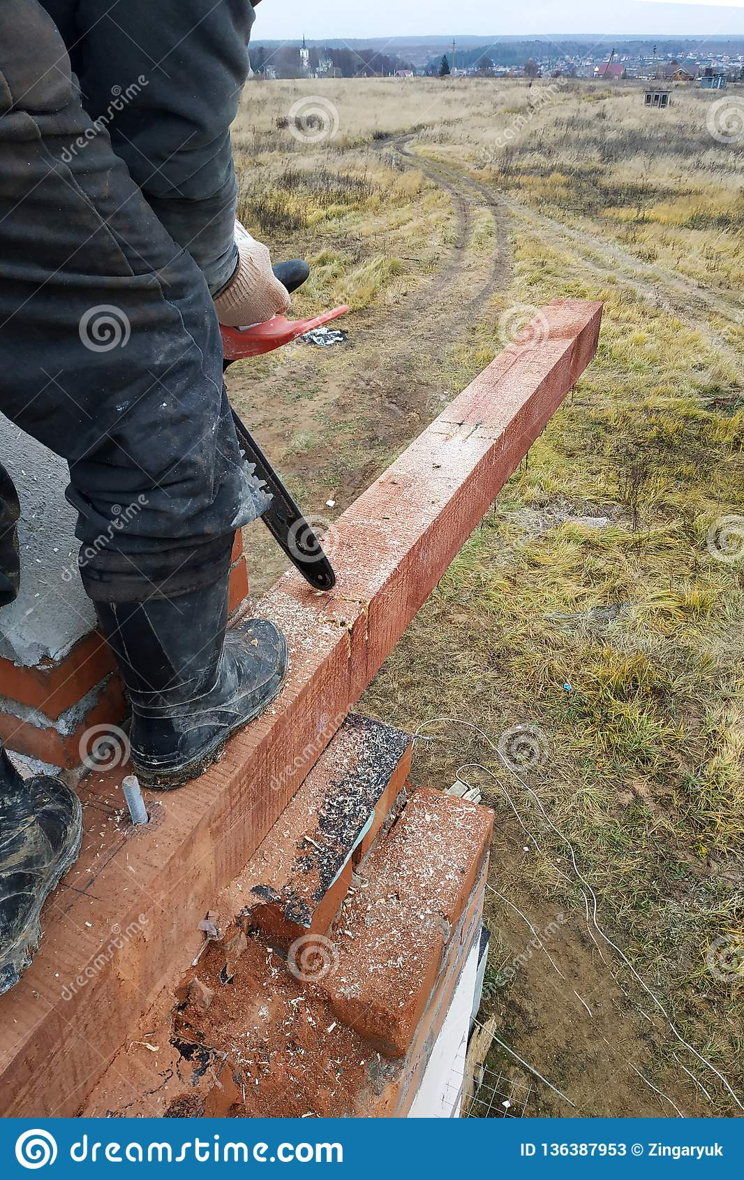 Inredningssnickaren med en chainsaw gör drack på en trästrålkonstruktion av hus