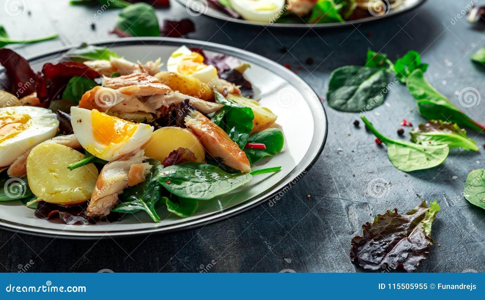 Insalata calda dello sgombro affumicato con la patata novella, uova, preparato verde della lattuga in un piatto