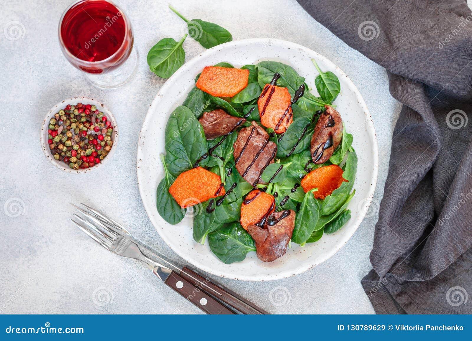 Insalata degli spinaci con il fegato di pollo e la zucca al forno con le spezie e balsamico caldi