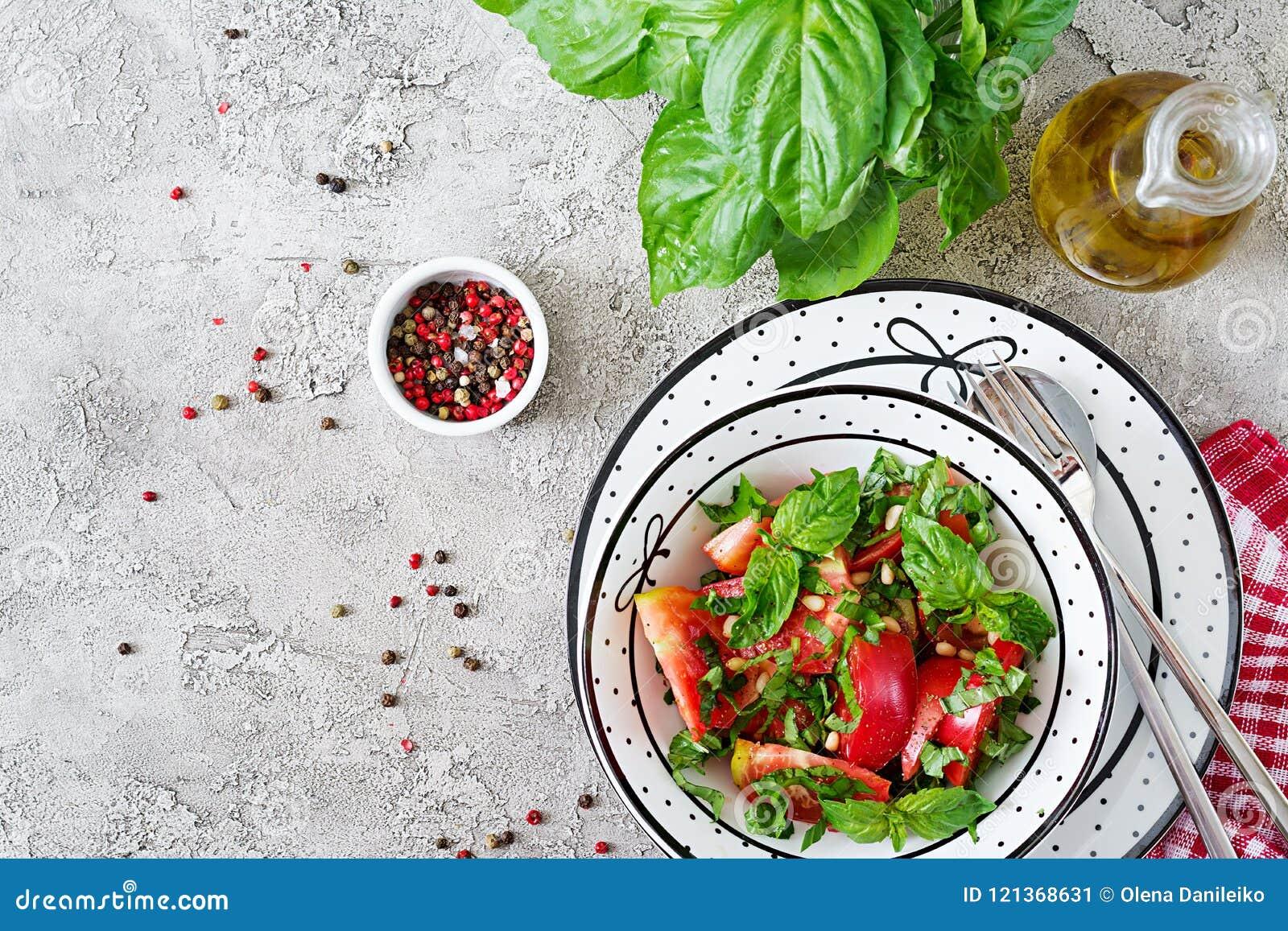 Insalata del pomodoro con basilico e pinoli in ciotola - aperitivo vegetariano sano dell alimento biologico di dieta del vegano