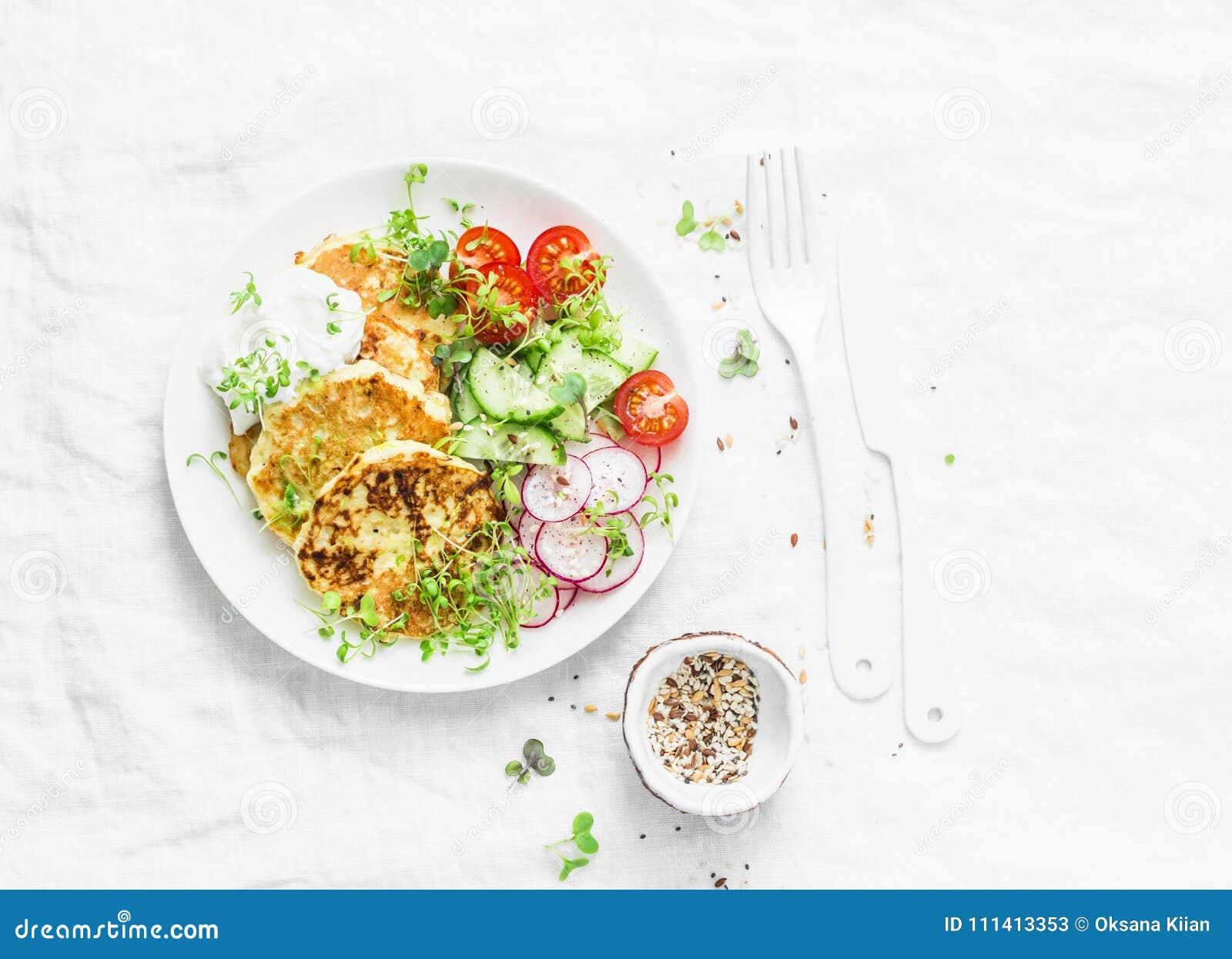 Insalata delle frittelle e degli ortaggi freschi dello zucchini di ricotta Cetrioli, pomodori ciliegia, ravanelli, micro verdi e
