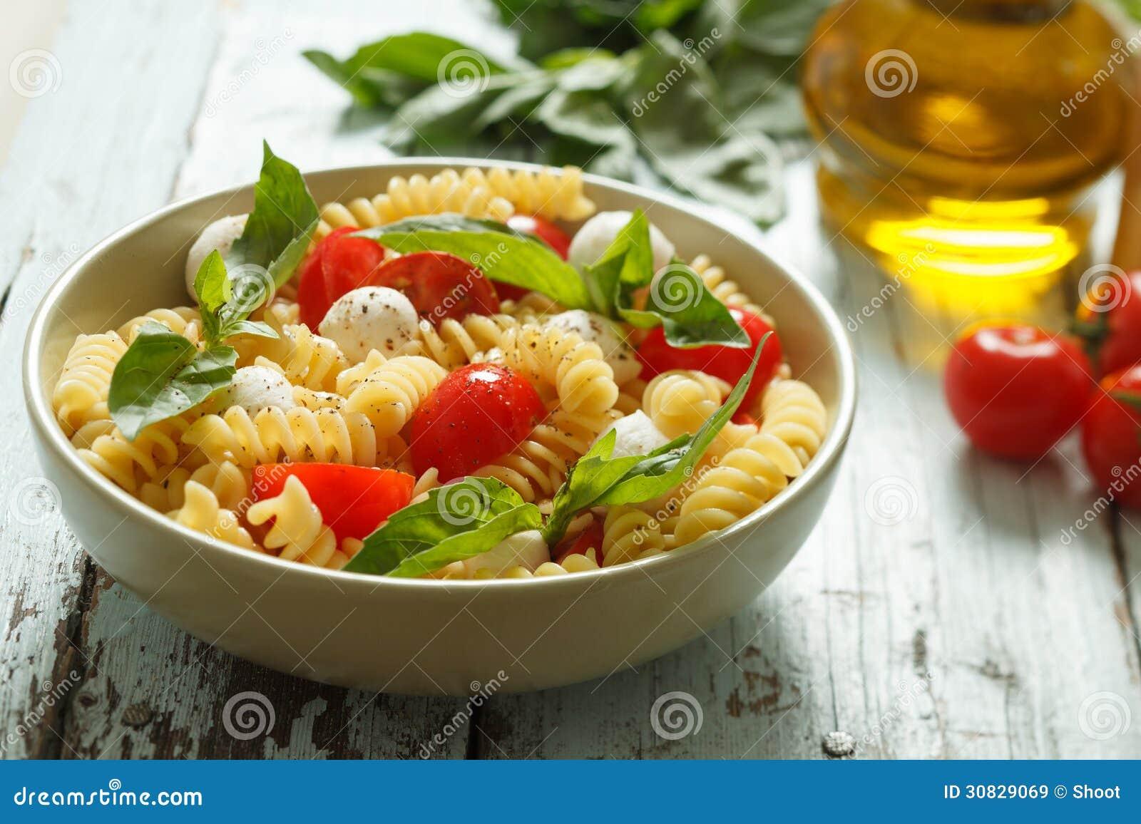 Insalata di pasta con i pomodori ciliegia e le foglie del basilico