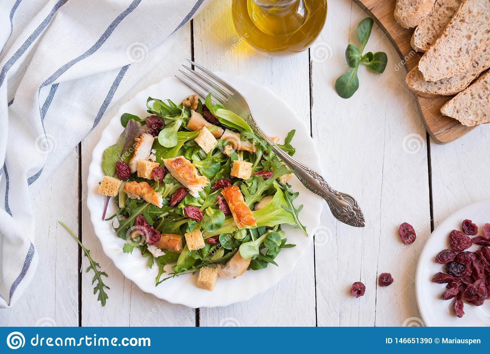 Insalata di verdura fresca con il pollo, arugola, crostini su legno bianco
