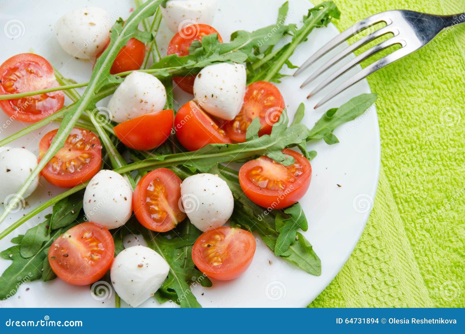Insalata di verdure della rucola, dei pomodori ciliegia e della mozzarella