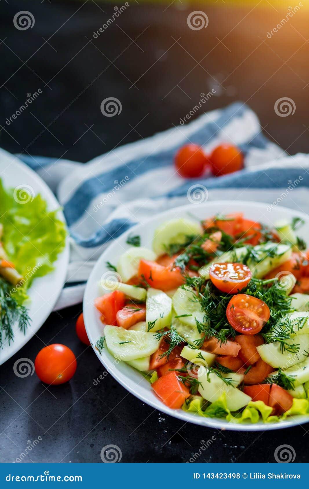 Insalata di verdure su un fondo nero, primo piano della molla fresca