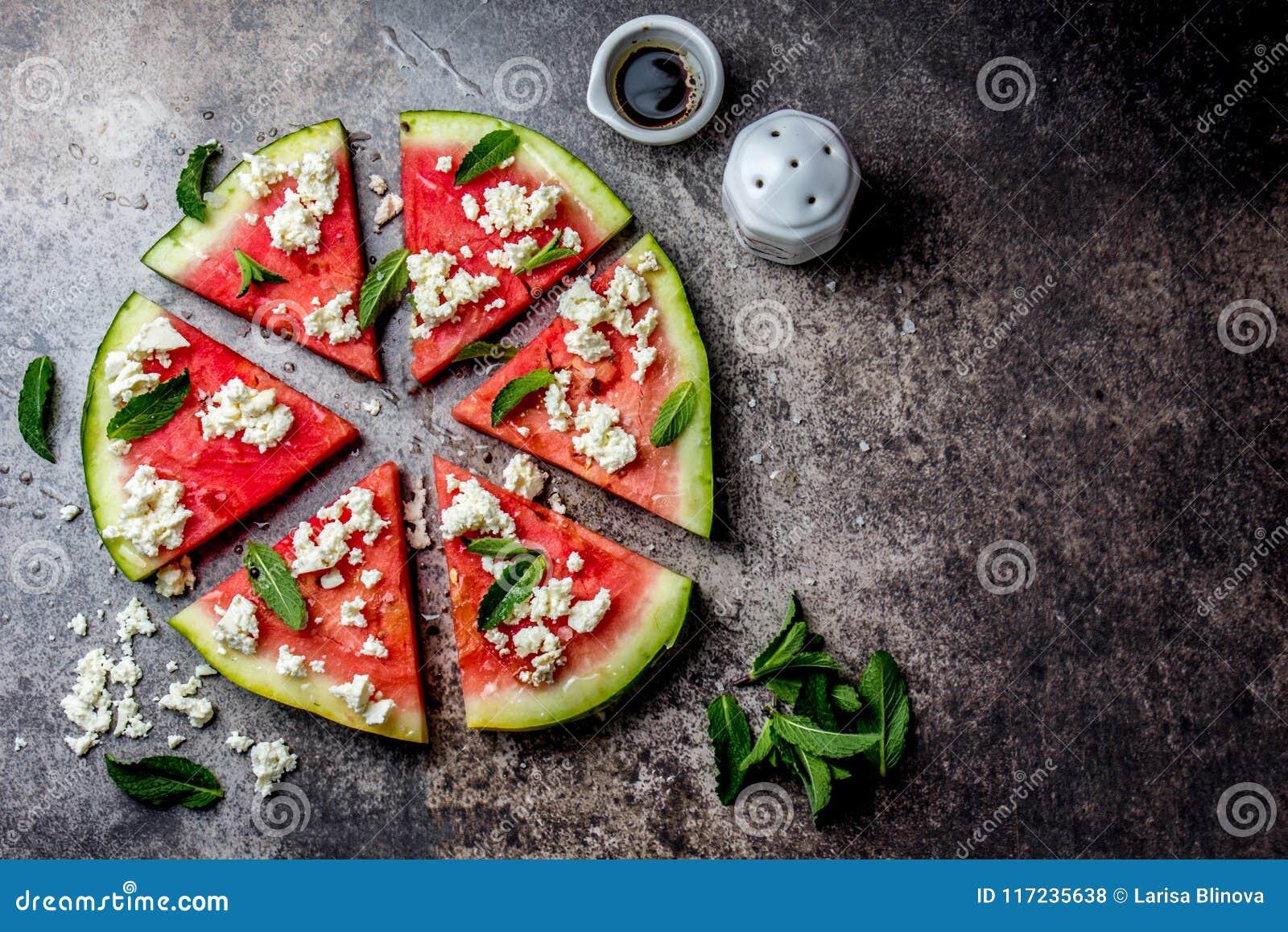 Insalata fresca della pizza dell anguria con feta, la menta, il sale e l olio su fondo di pietra