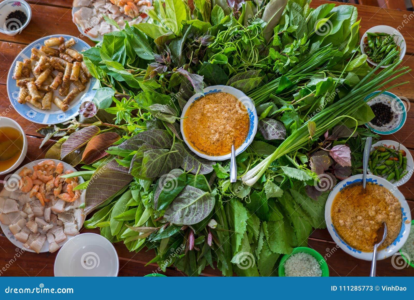Insalata peculiare delle erbe in Kon Tum, Vietnam Facendo uso delle foglie per fare un contenitore a forma di cono per mettere l