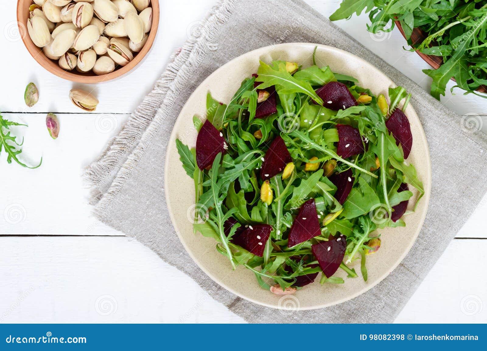 Insalata piccante del vegano delle barbabietole, rucola, pistacchi su un piatto su un fondo bianco