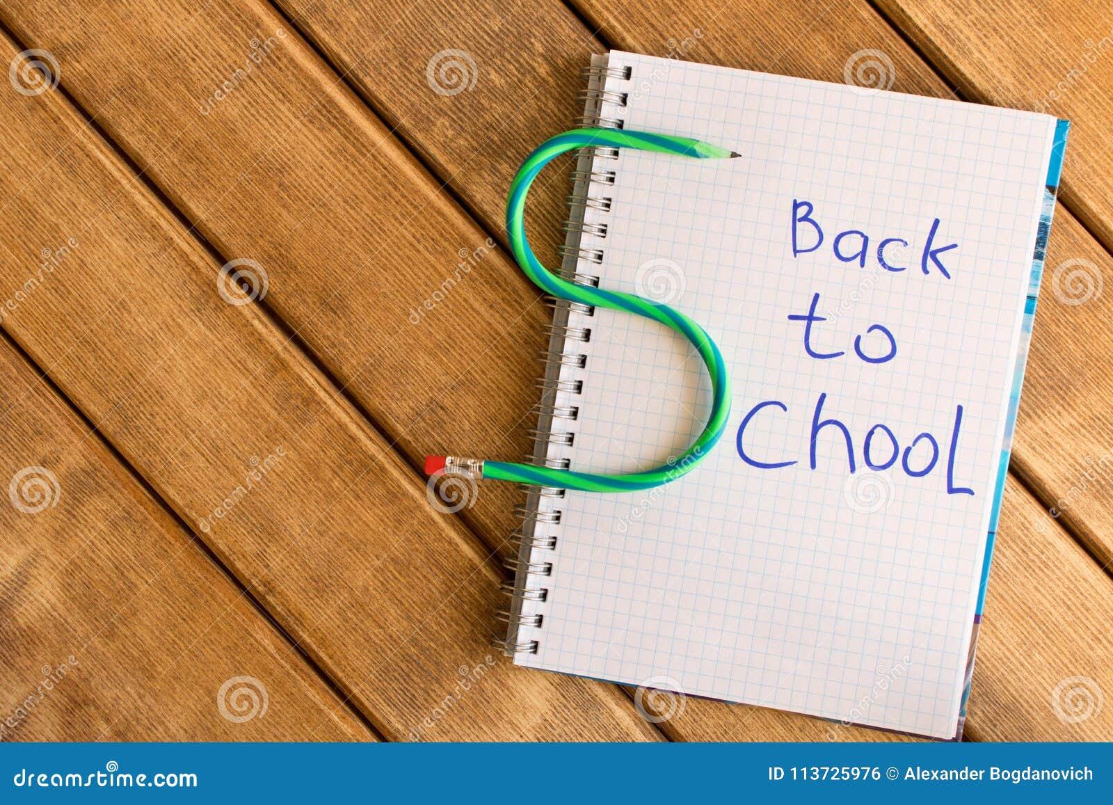 Inscrição de volta à escola no bloco de notas no fundo de madeira
