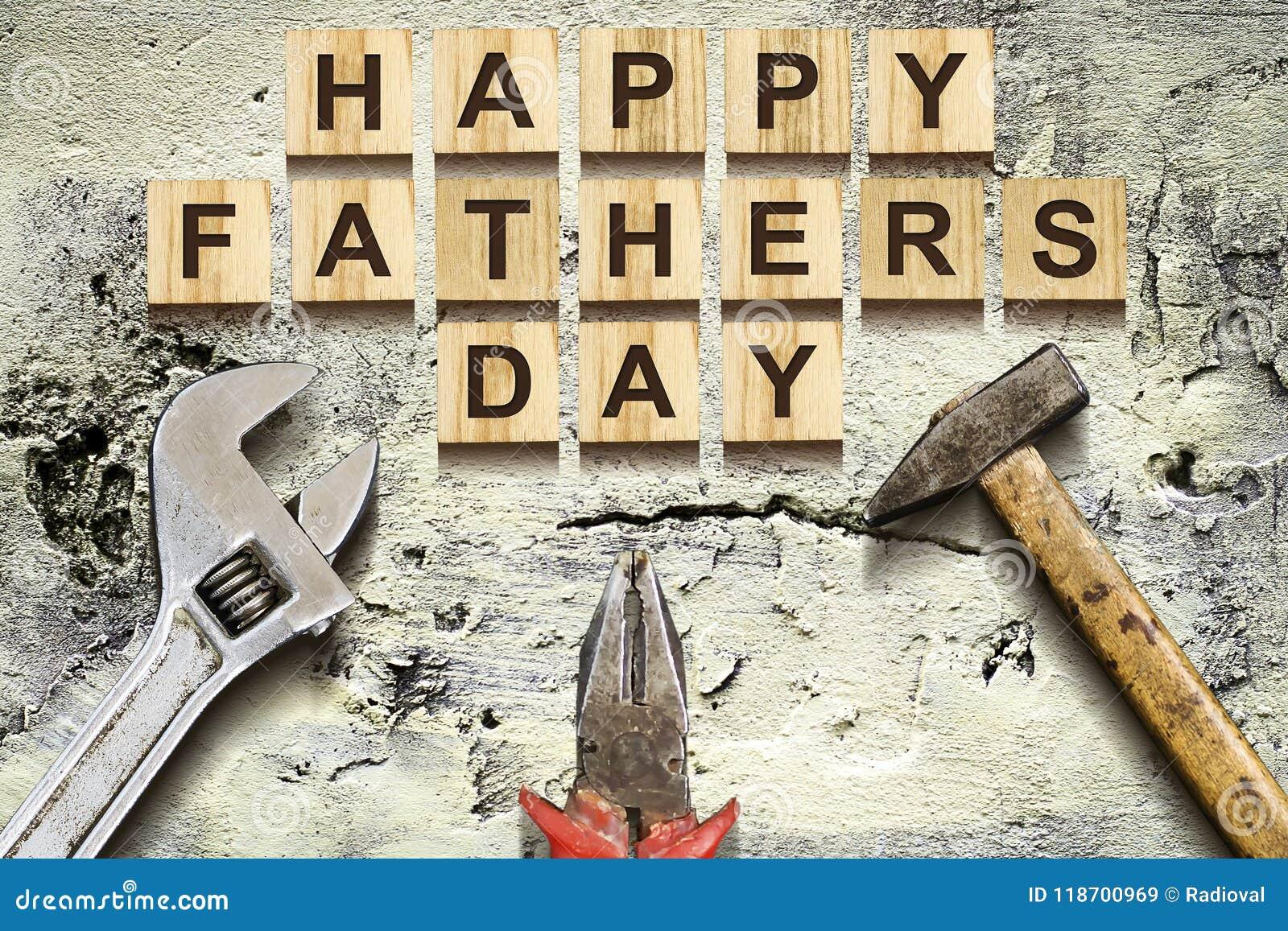 Inscrição feliz do dia de pais em cubos de madeira com ferramentas de funcionamento em um muro de cimento velho do vintage Concei