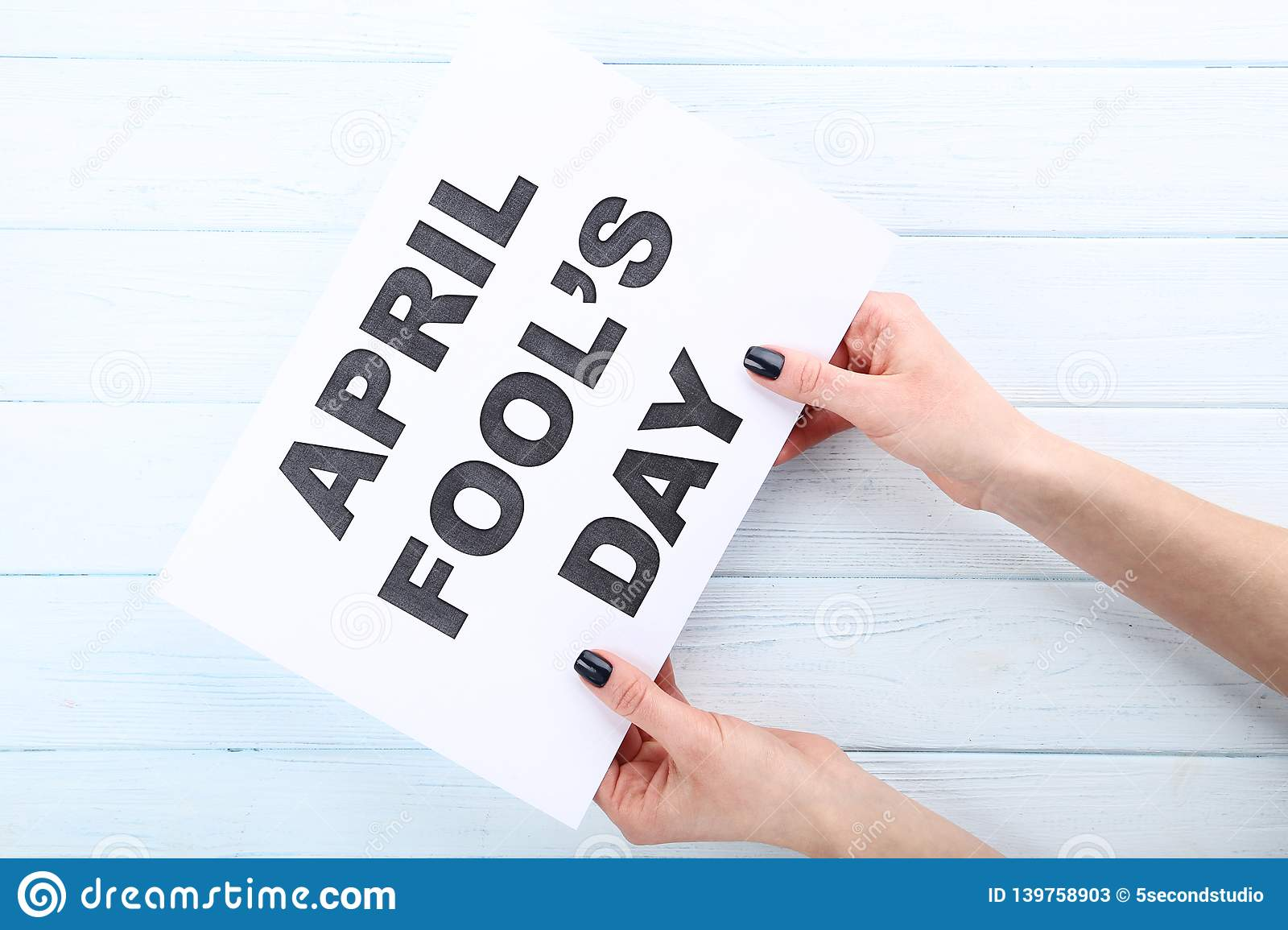 Inscription April Fool\'s Day on paper in female hands stock photos