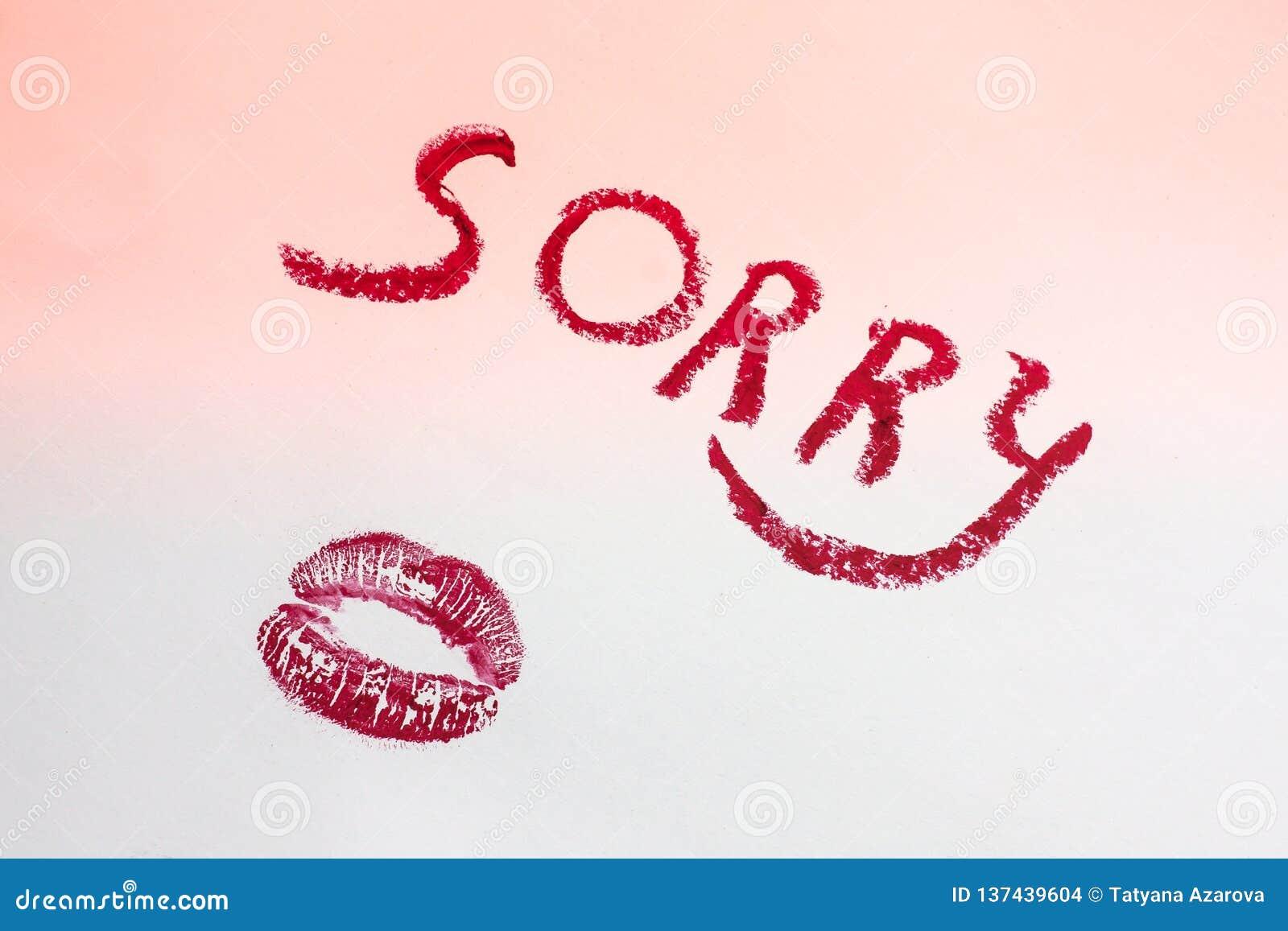 Inscription désolée dans les lettres rouges du rouge à lèvres sur une feuille du papier blanche rose, copie de rouge à lèvres sou