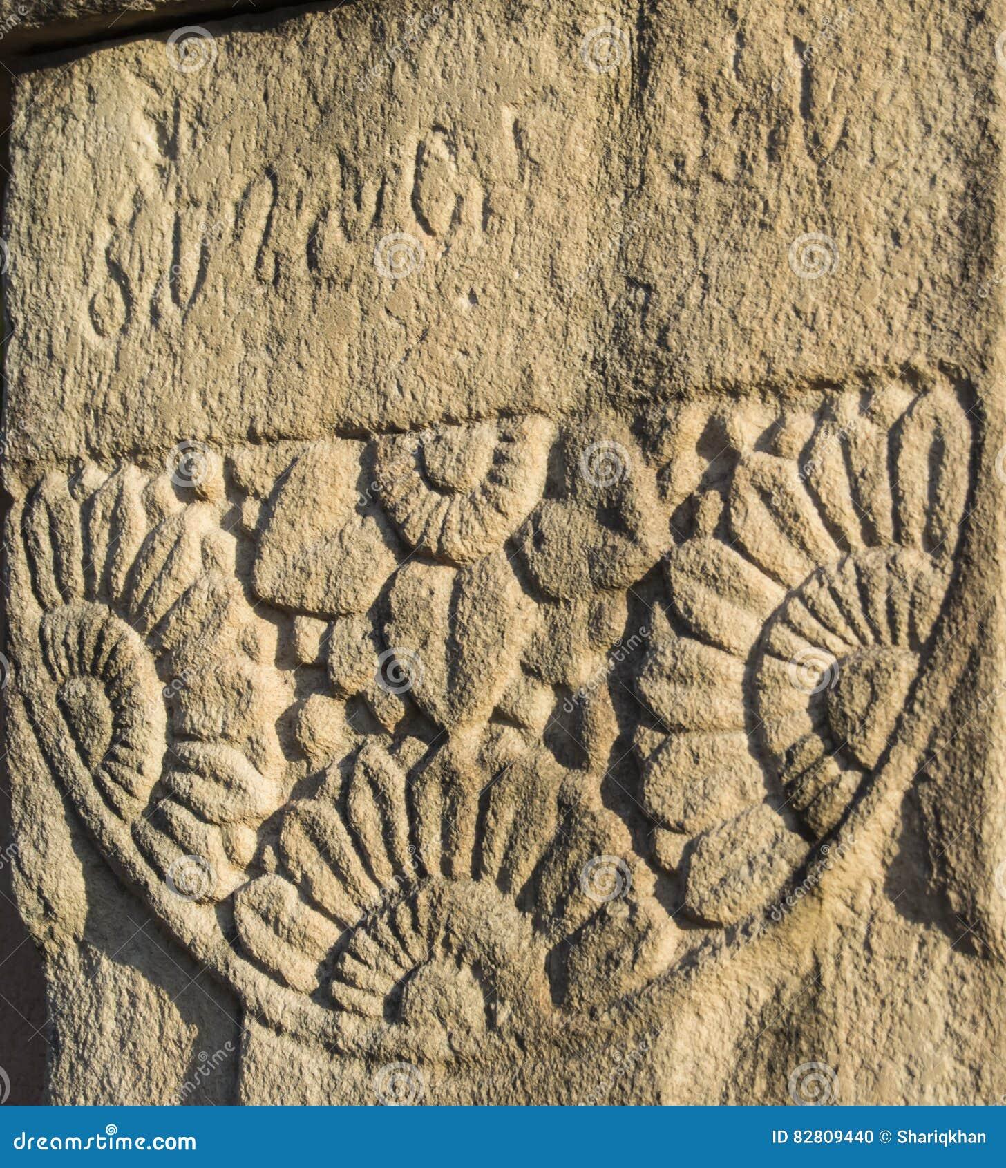 Inscription de Brahmi et motif Sanchi de pierre