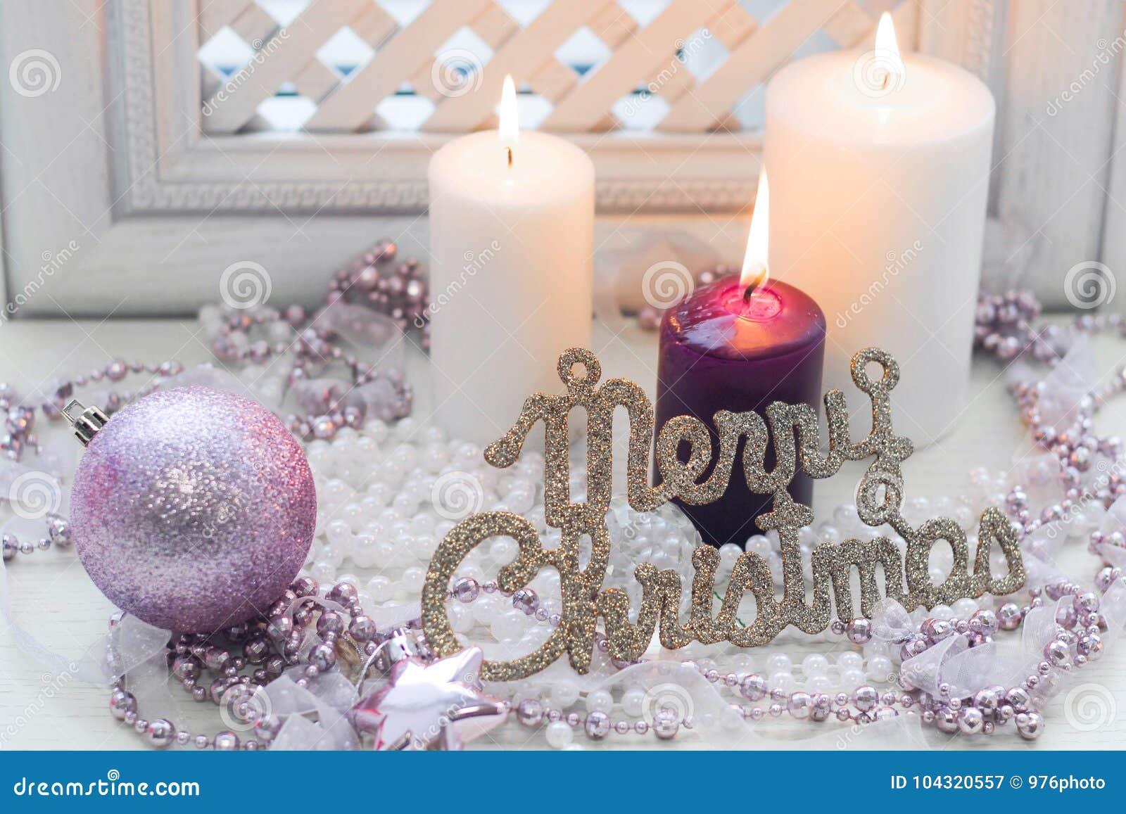 Inscription de Joyeux Noël, bougies brûlantes et décorations roses sensibles