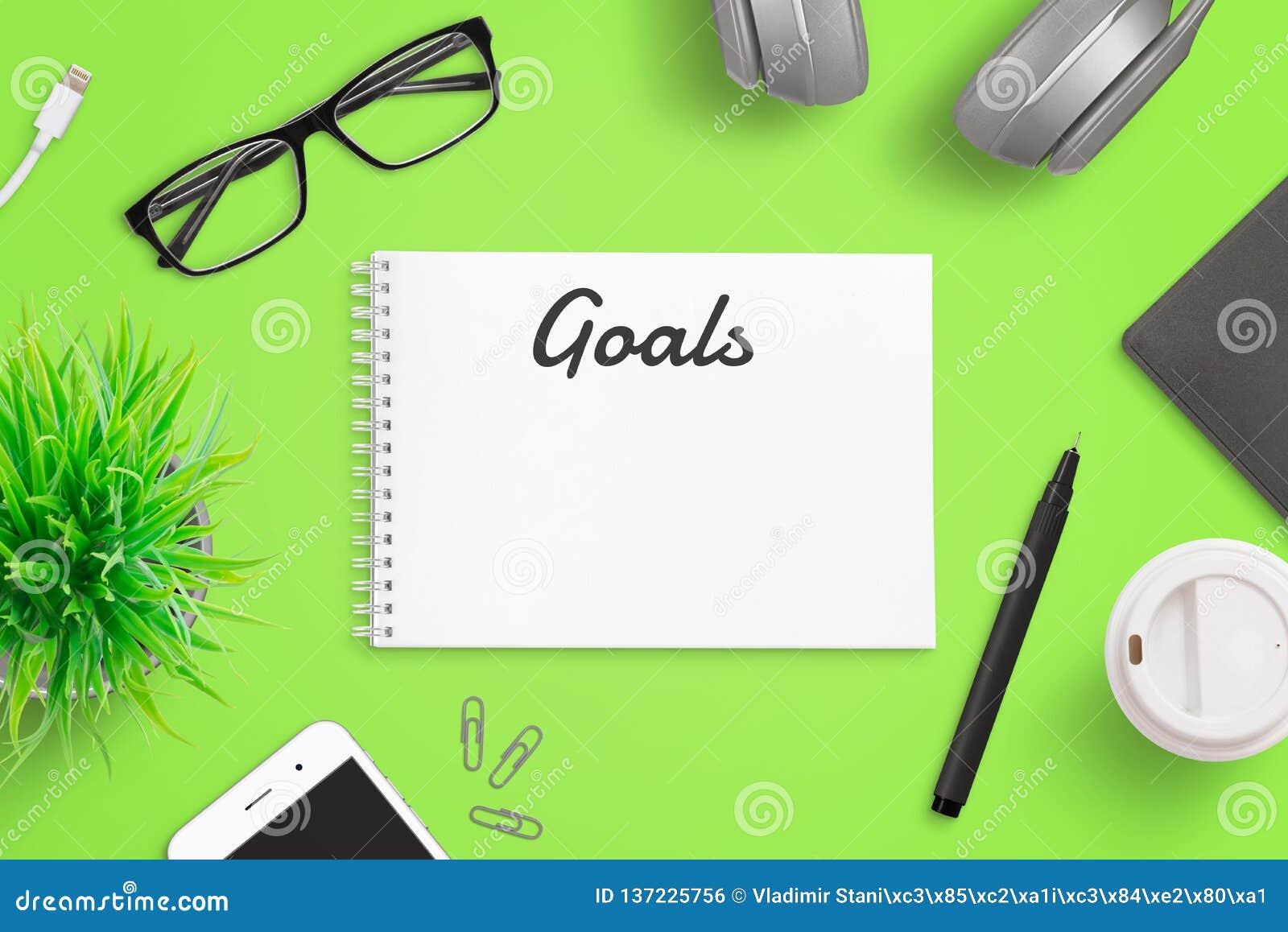 Inscription des buts sur le concept de page de bloc-notes Bureau vert avec le téléphone intelligent, verres, dossier, café, usine