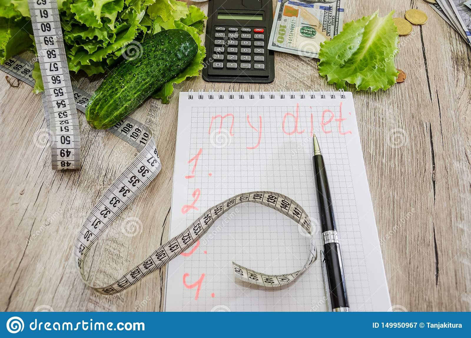 The inscription `diet` on a notebook, dollars, coins and vegetables on the table