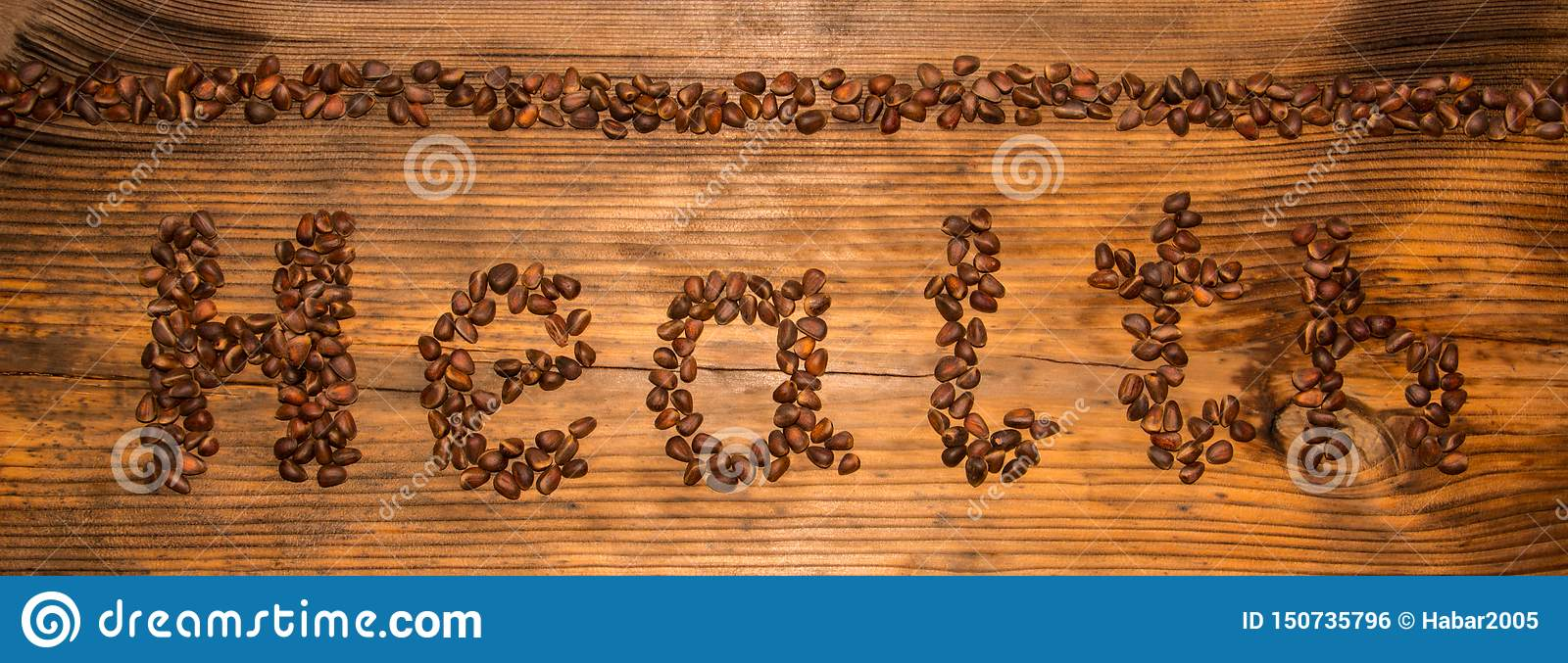 Inscription health from pine nuts on a wooden board background.