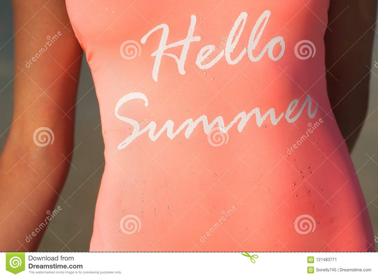 The inscription is hello summer on a pink swimsuit. Girl in pink bathing suit close-up with droplets