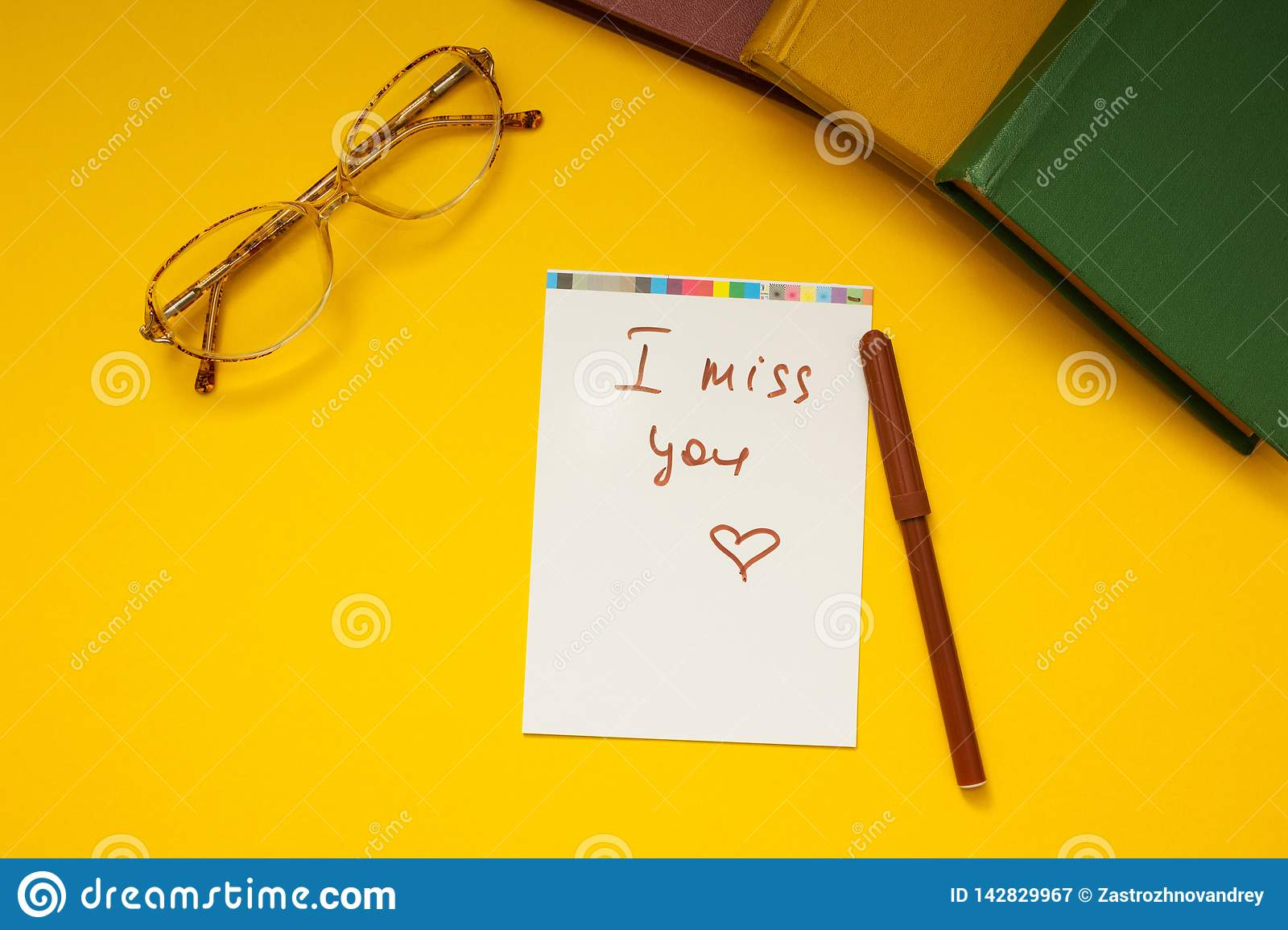 The inscription `I miss you` on a yellow background, glasses and books together.