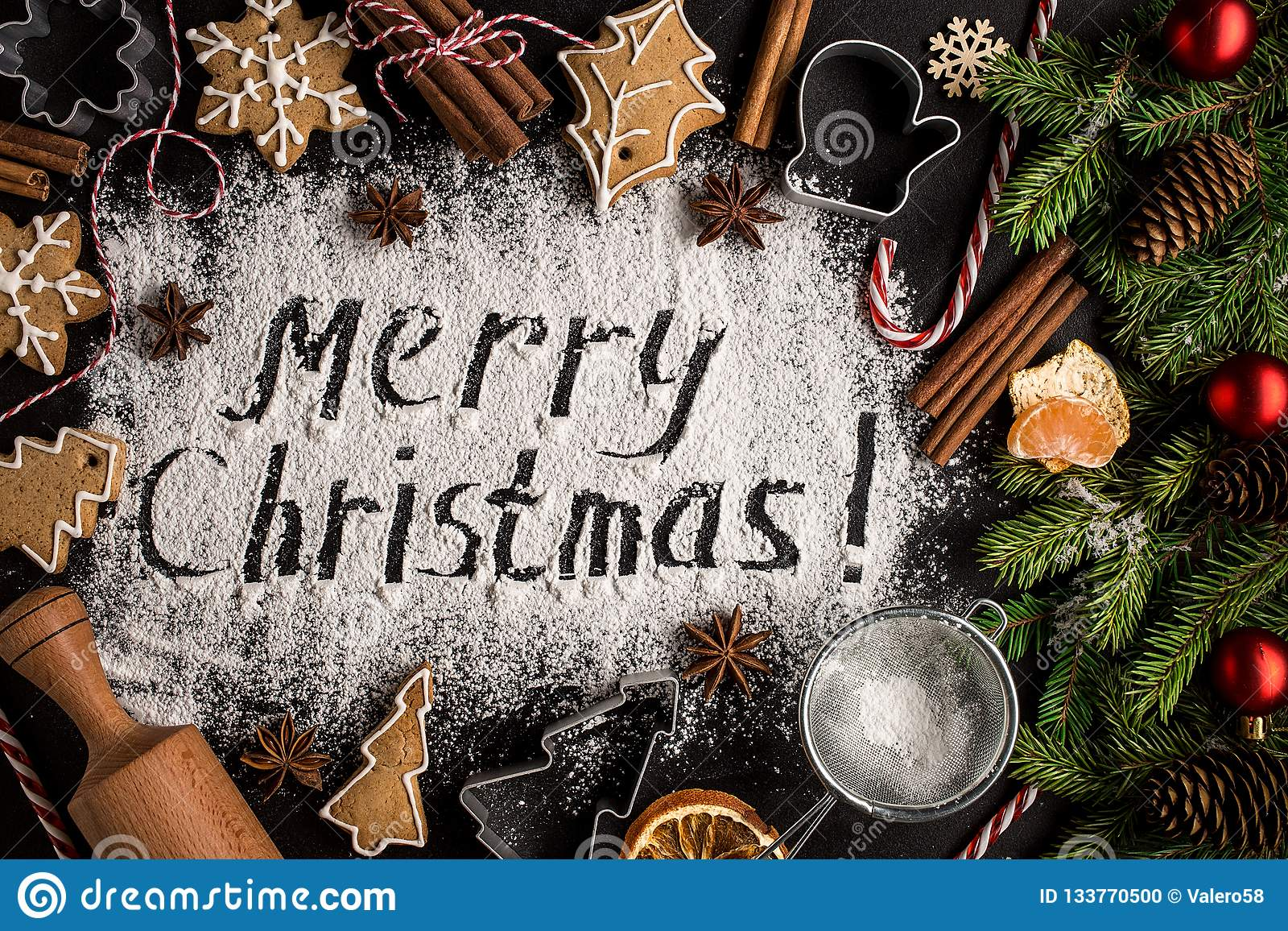 Inscription MERRY CHRISTMAS on powdered sugar background.