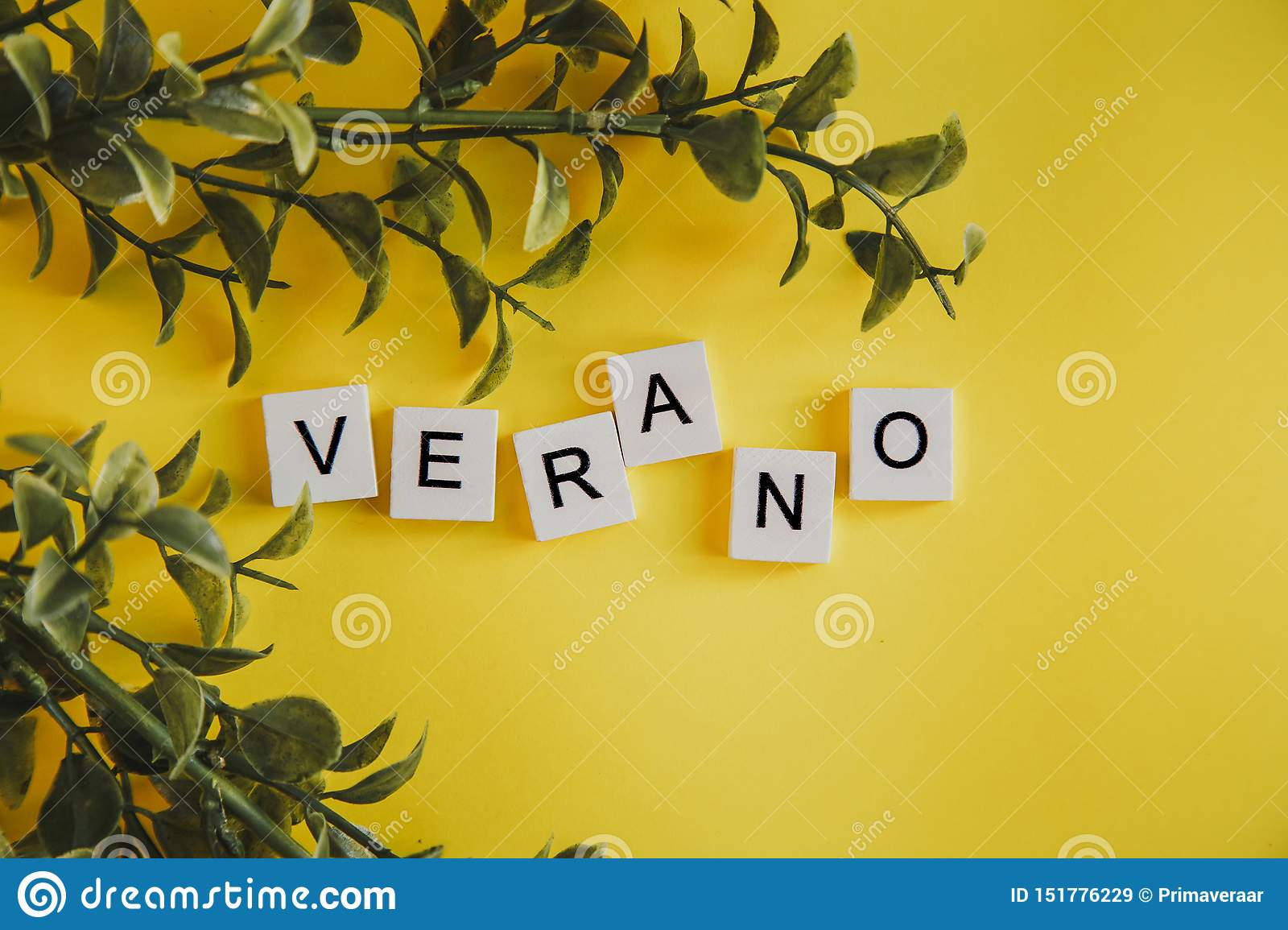 The inscription verano in spanish on the letters of the keyboard on a yellow background with branches of flowers