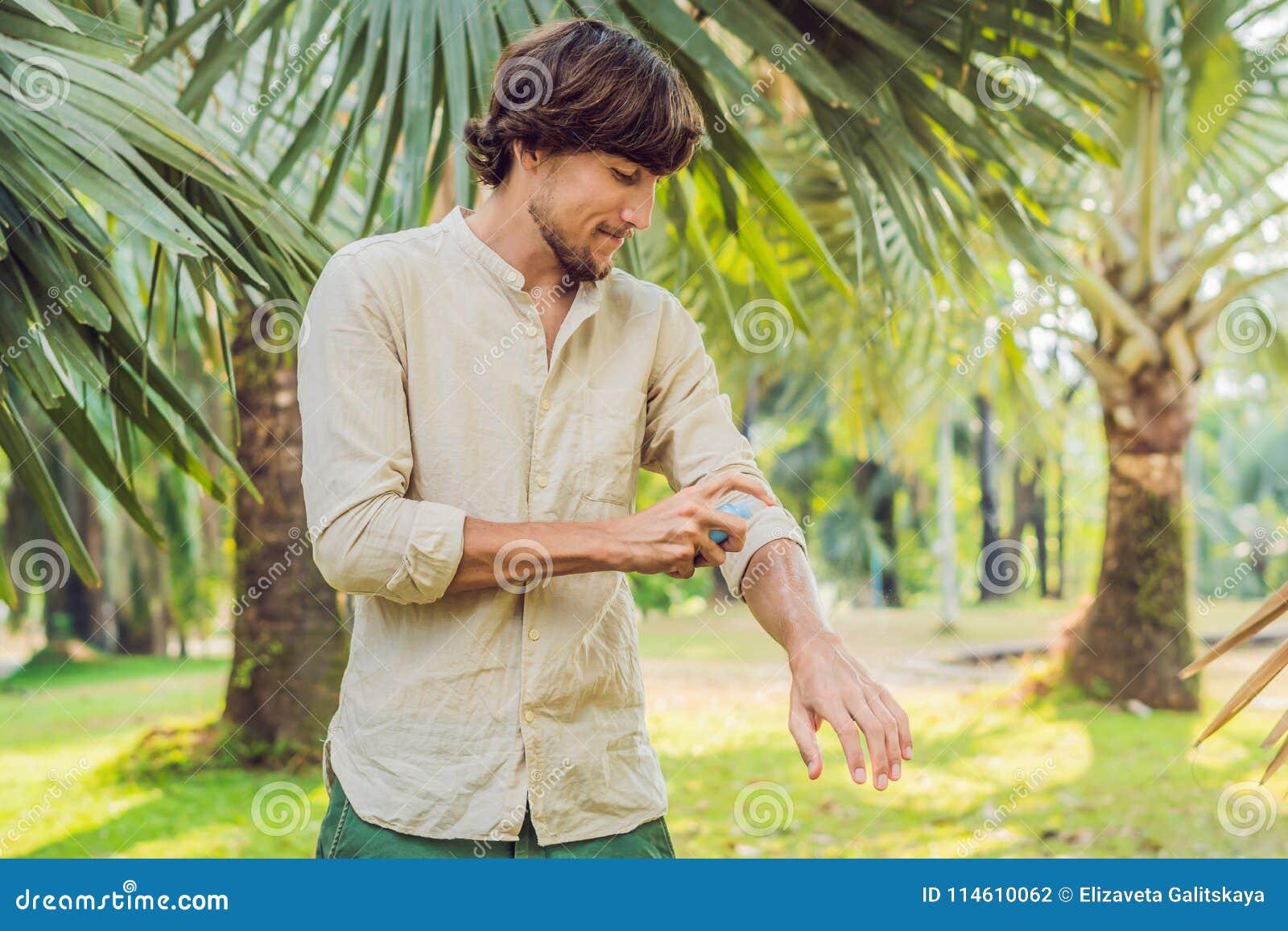 Insectifuge de pulvérisation de moustique de jeune homme dans le forrest, protection d insecte