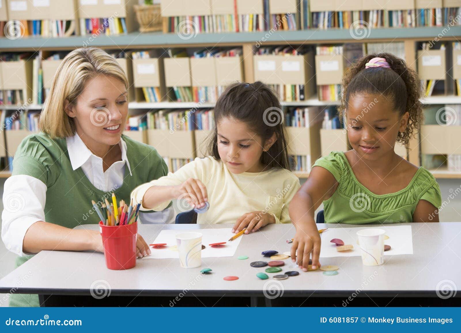Insegnante che si siede con gli allievi nel codice categoria di arte
