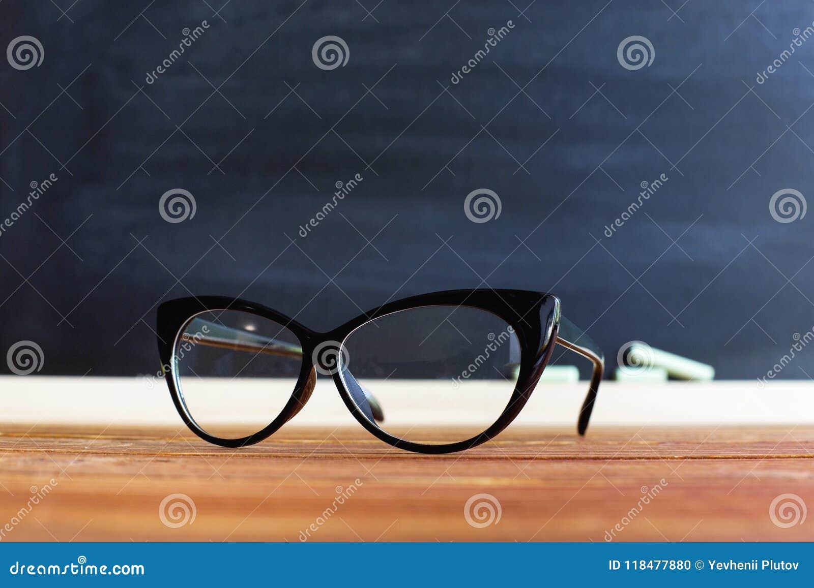 Insegnante di vetro su una tavola, contro un fondo della lavagna con gesso Concetto per il giorno degli insegnanti Copi lo spazio