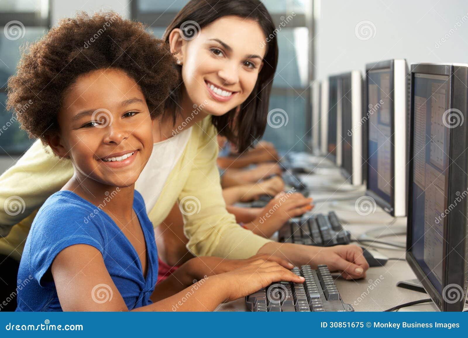 Insegnante Helping Elelmentary Students che lavora ai computer