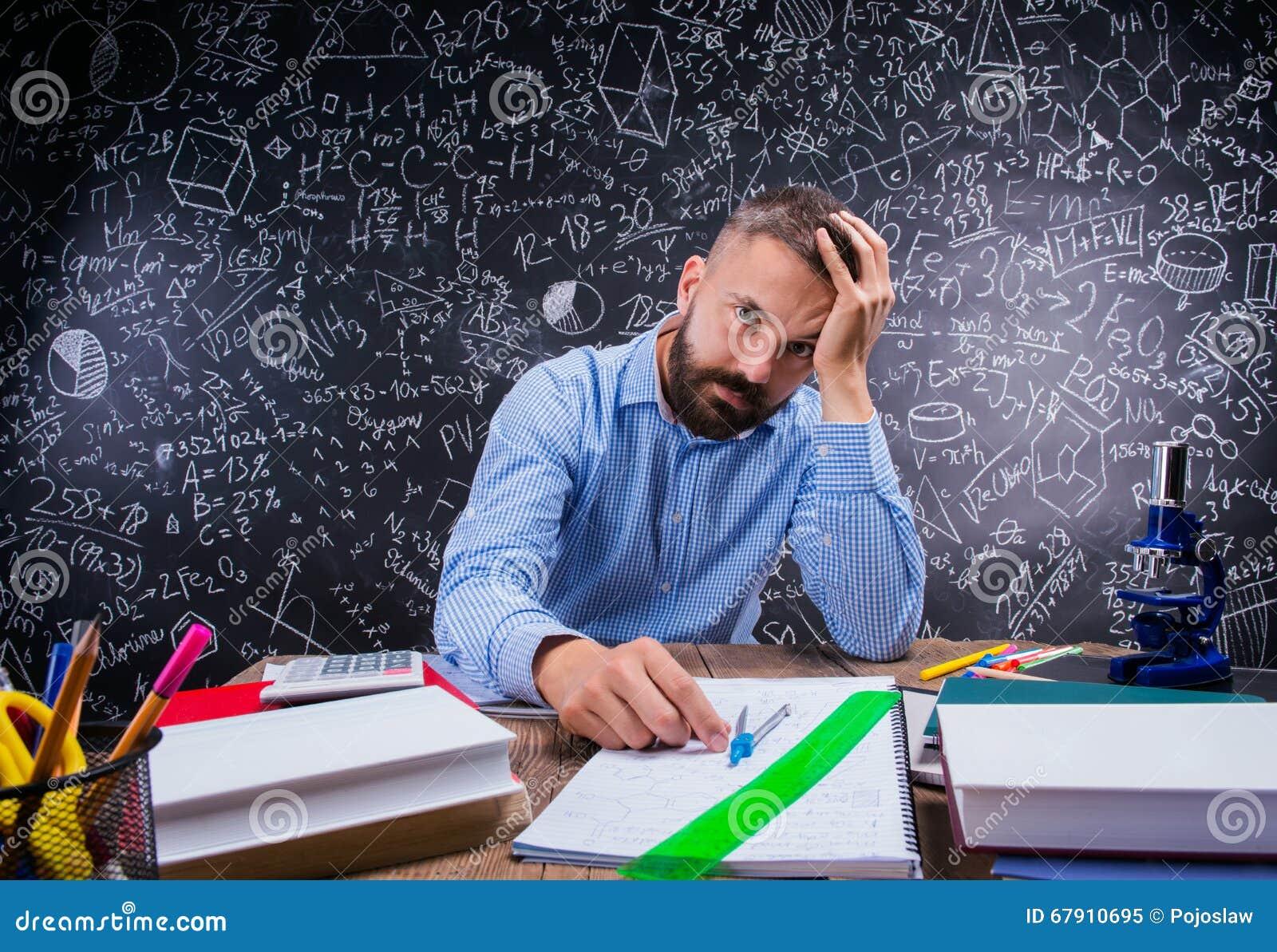 Insegnante turbato allo scrittorio, rifornimenti di scuola, tenenti testa, lavagna