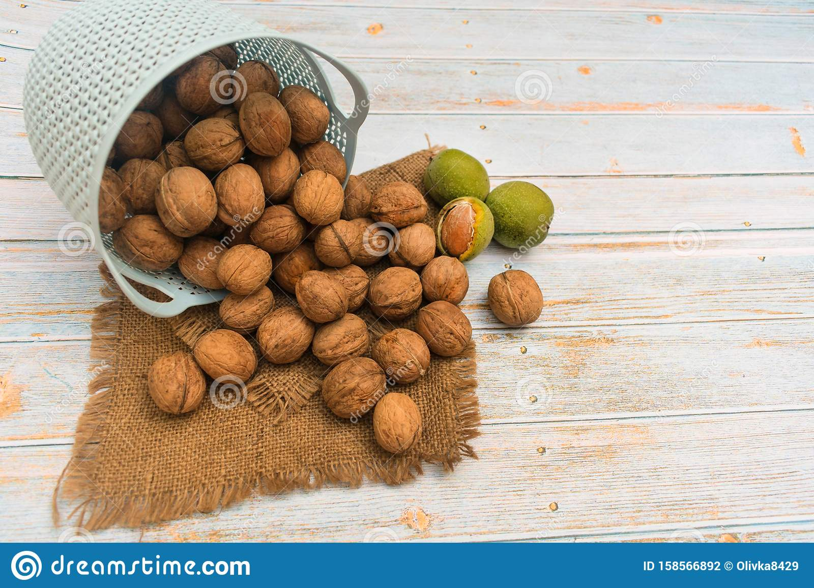 Inshell walnuts in a basket on a light wooden background.