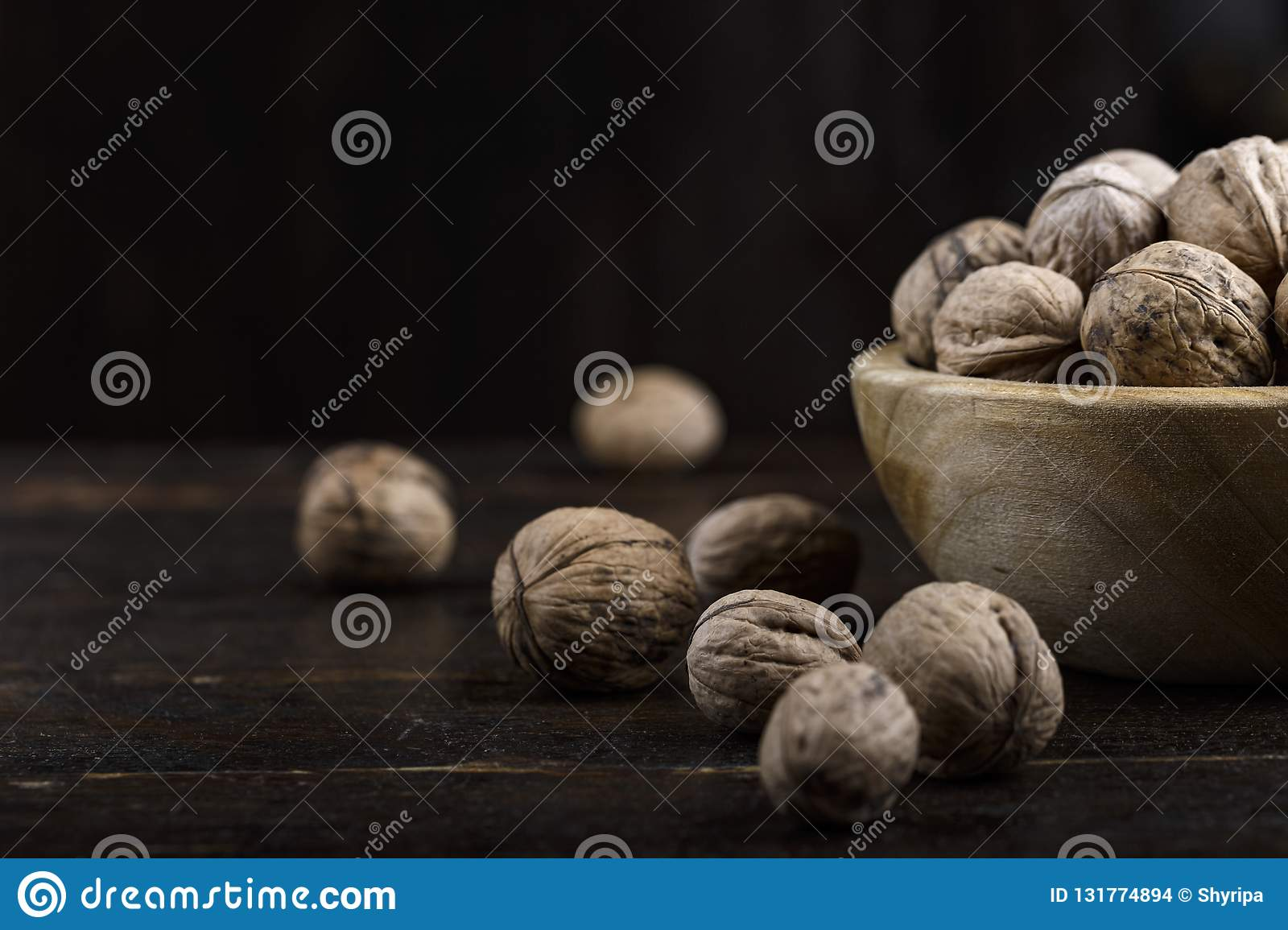 inshell whole walnuts on dark wooden background.