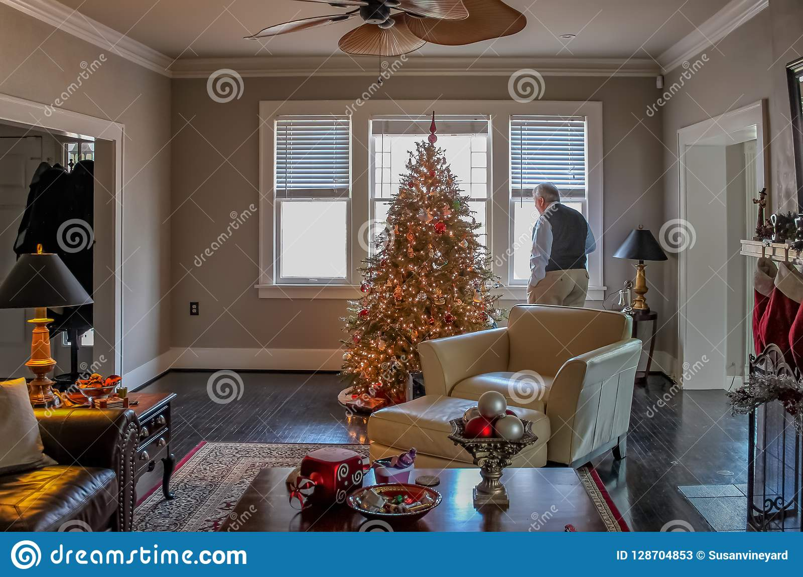 Inside elegant home decorated for Christmas with tree and stockings an older man looks out window