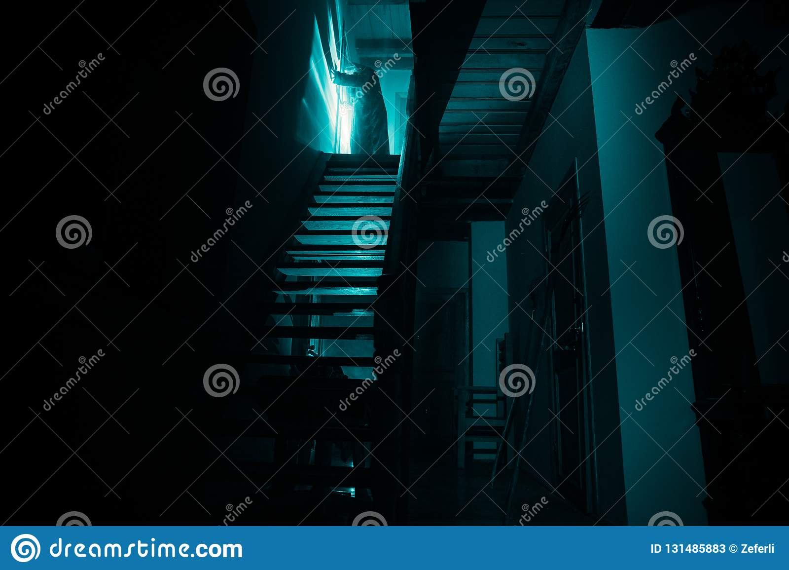Inside of old creepy abandoned mansion. Silhouette of horror ghost standing on castle stairs to the basement. Spooky dungeon stone