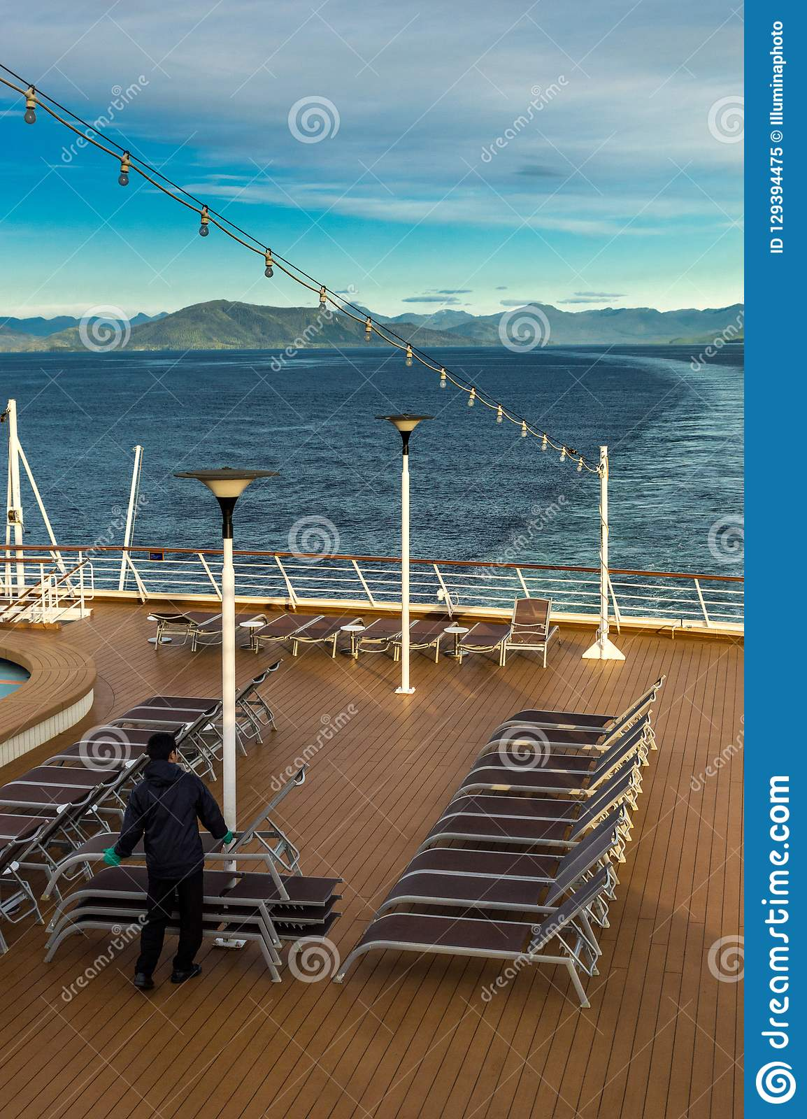 Inside Passage, BC, Canada - September 13, 2018: Cruise ship worker stacking outdoor loungers in the early evening.