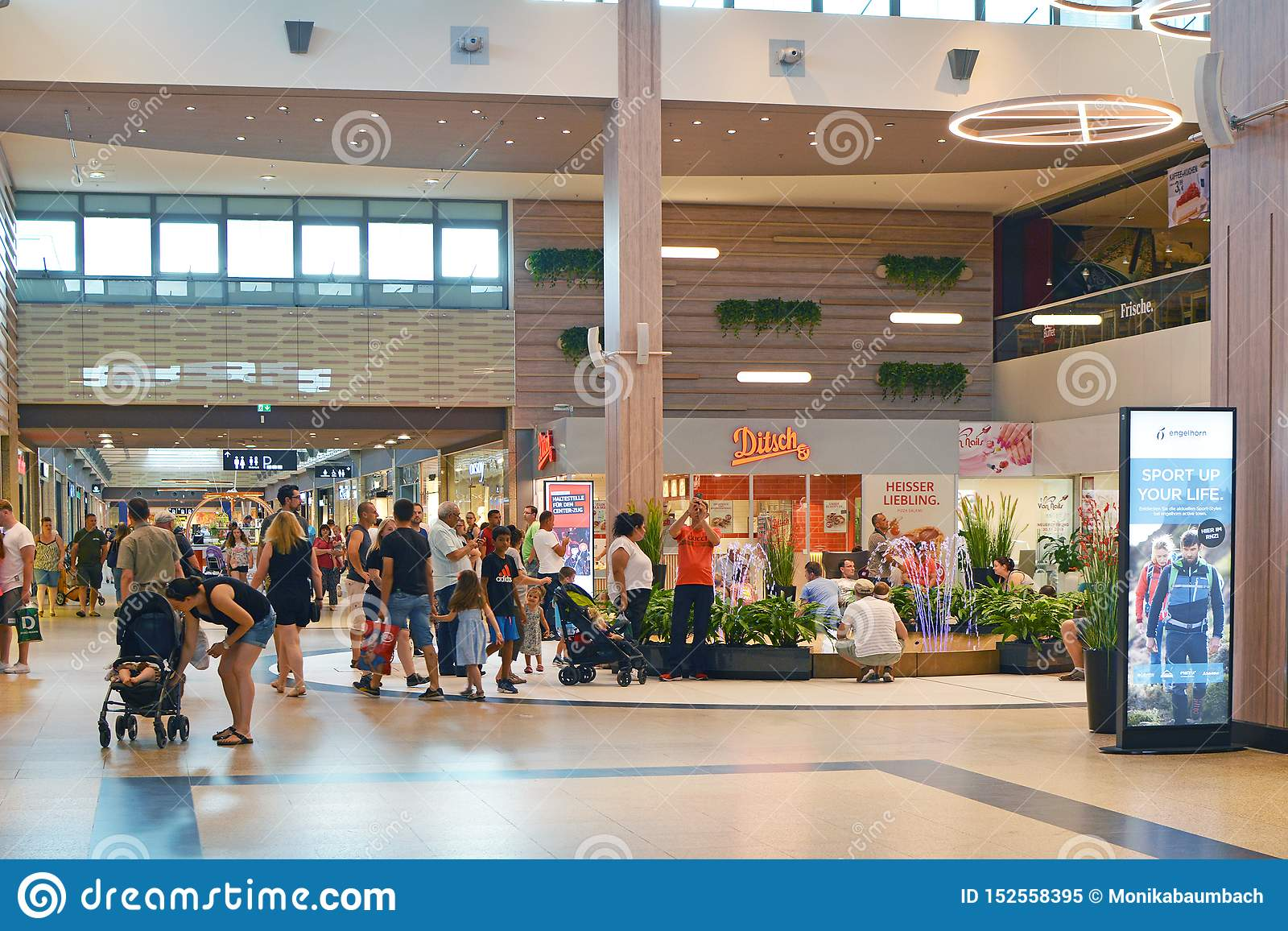 Inside of shopping mall called `Rhein Neckar Zentrum` with people shopping on a busy day