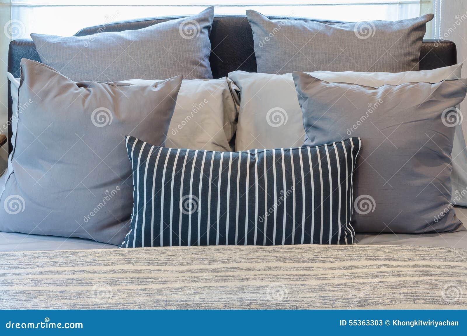 Insieme dei cuscini sul letto moderno in camera da letto