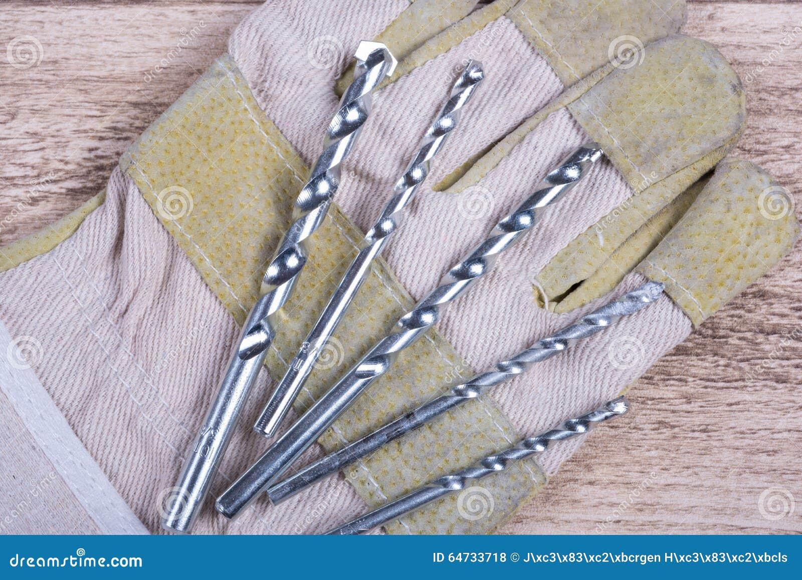 Insieme dei trapani di pietra su un guanto di lavoro che si trova su una tavola di legno