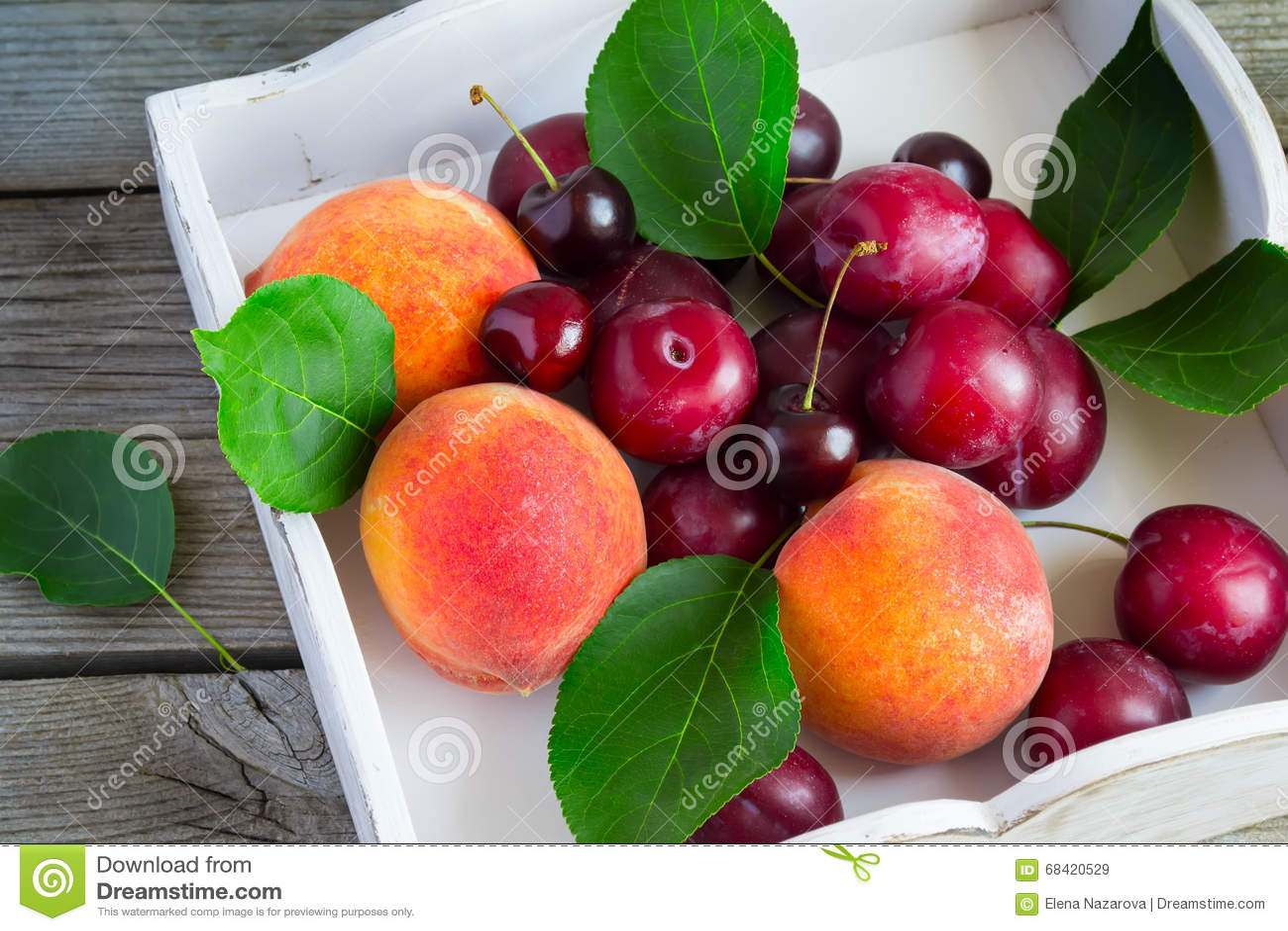 Insieme di frutta: pesche, prugne, ciliege su un vassoio bianco