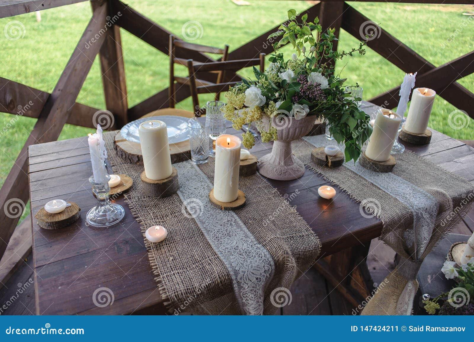 Insieme di legno della tavola con le candele ed i fiori all aperto