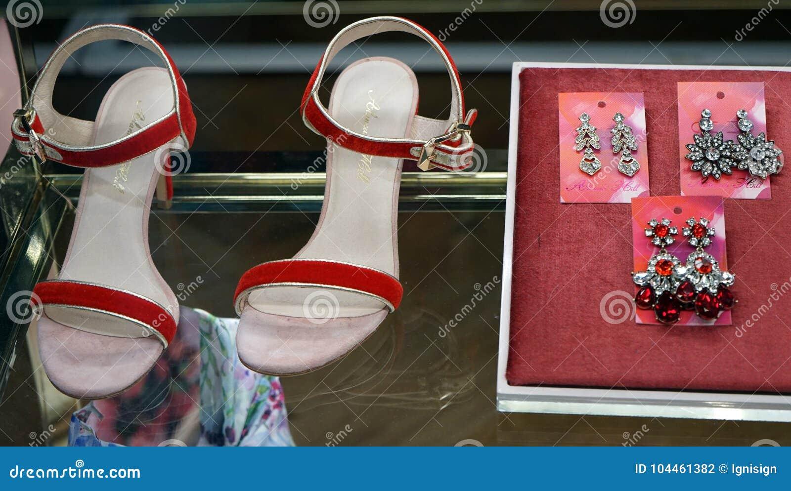 Insieme moderno degli accessori rossi del ` s delle donne - sandali ed orecchini sull esposizione della finestra