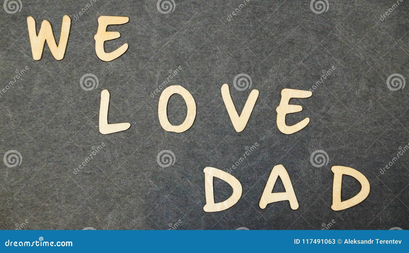 Inskrift`en älskar vi farsa` vikt av träbokstäver på en svart tabell