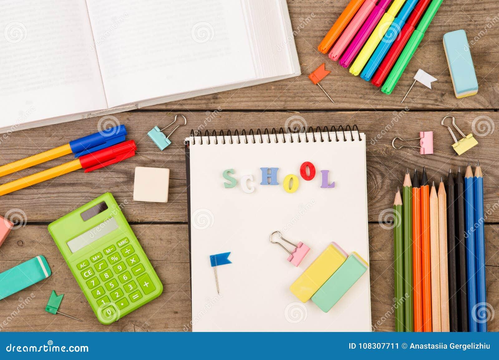 Inskrypcja & x22; school& x22; , książka, kalkulator, notepad i inny materiały na brown drewnianym stole,