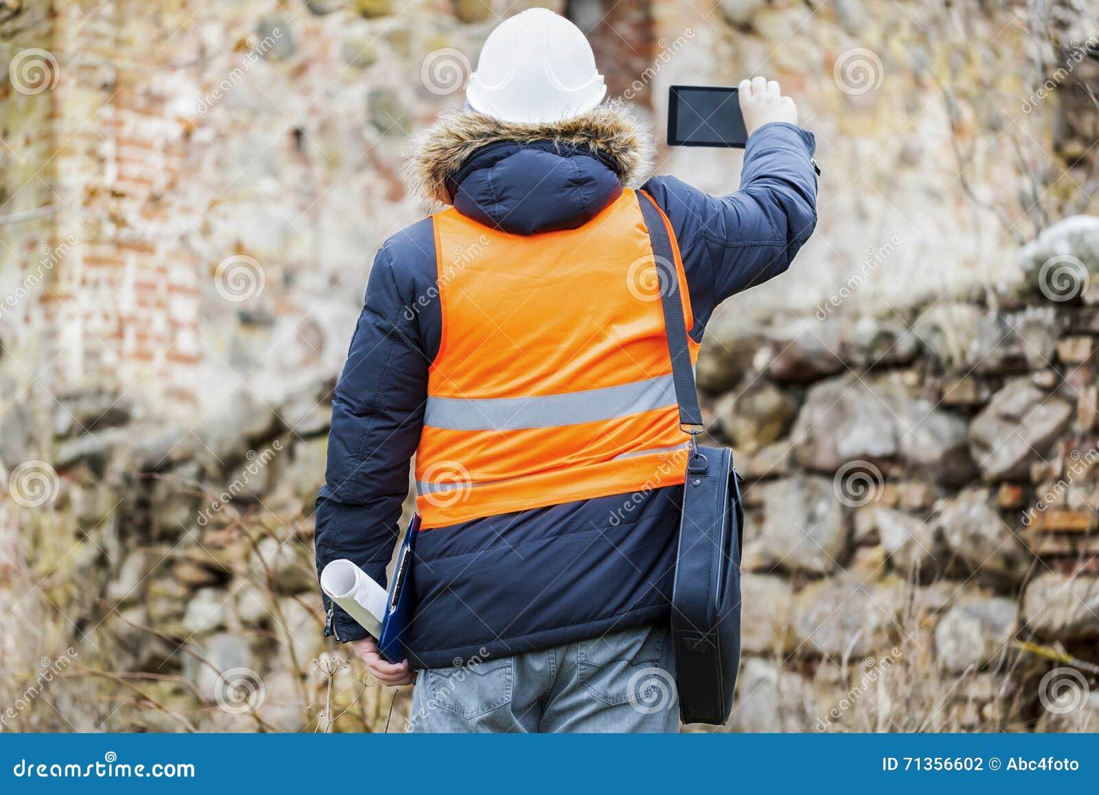 Inspecteurs des bâtiments avec la tablette à de vieilles ruines