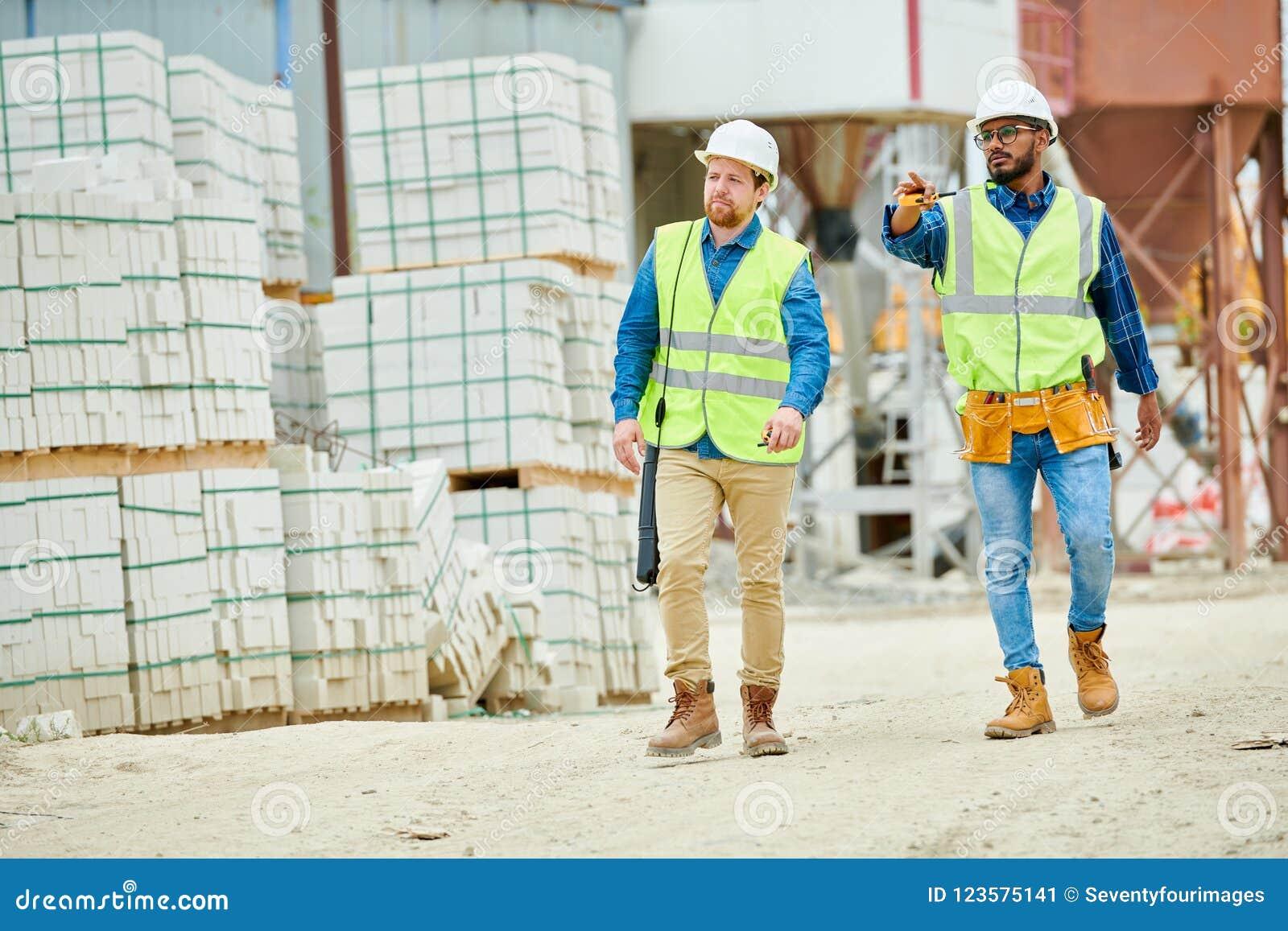 Inspecteurs des bâtiments marchant sur le chantier de construction