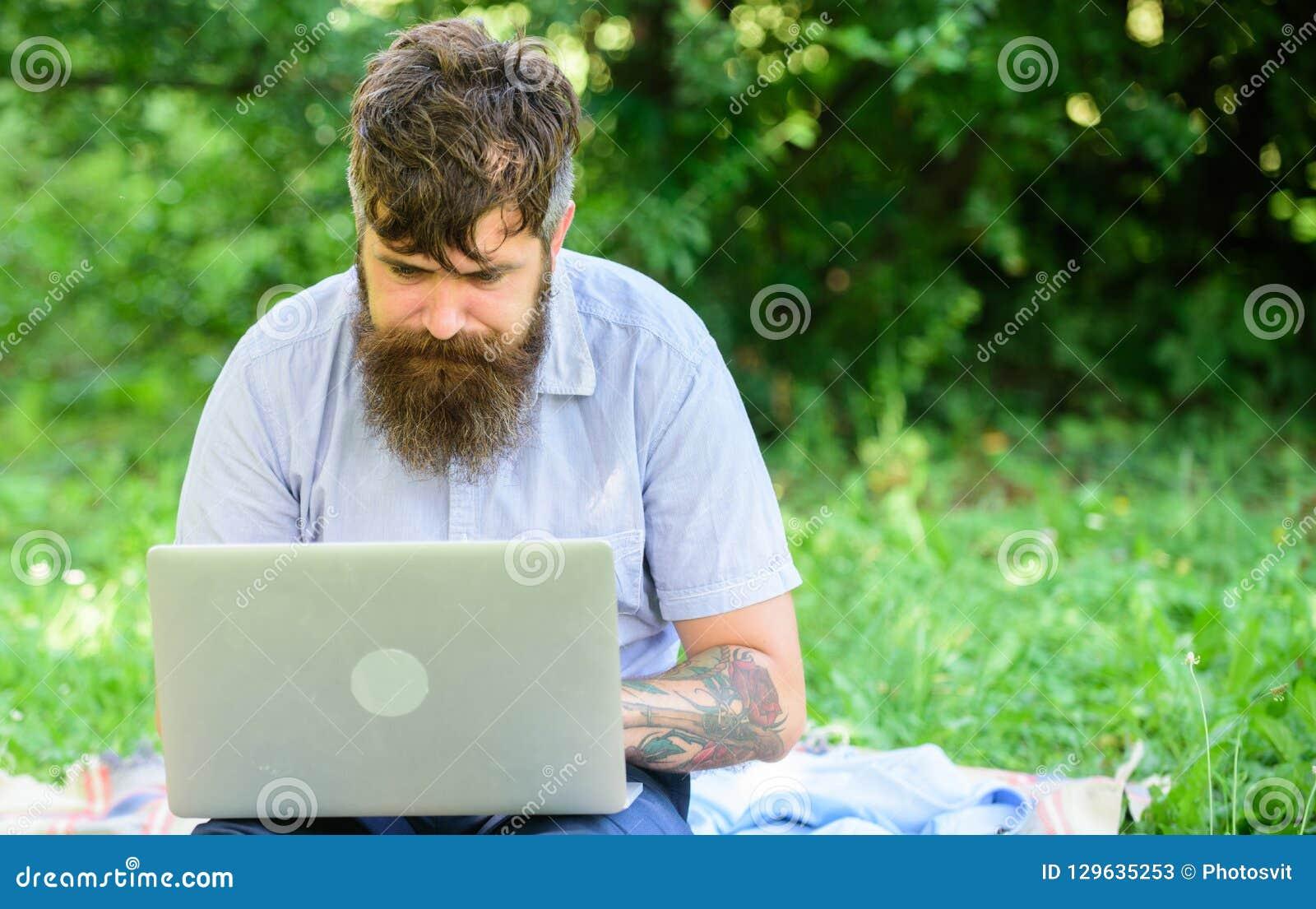 Inspiração para publicar em blogs Procurando a inspiração Blogger que torna-se inspirado por natureza O homem farpado com portáti