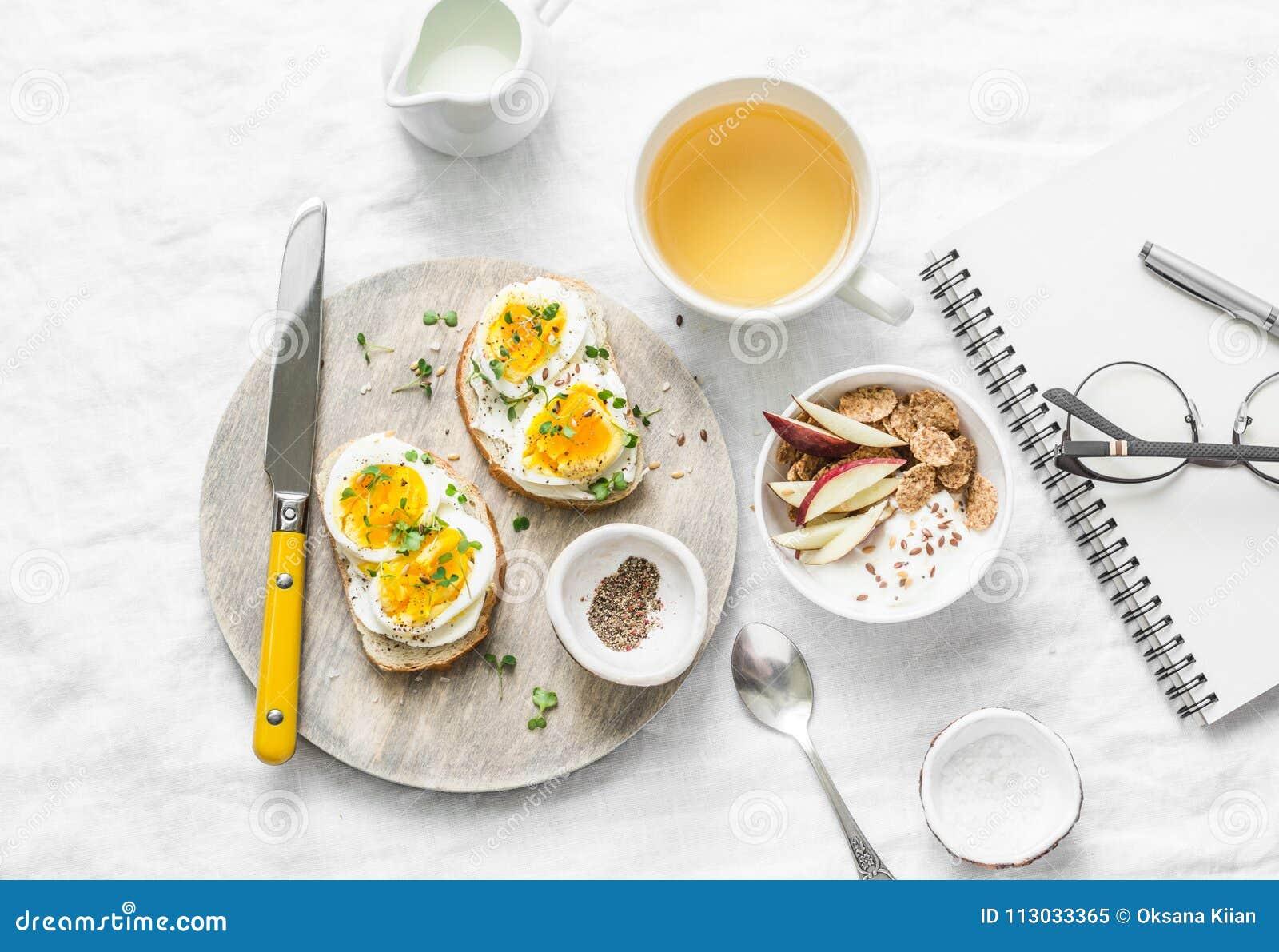 Inspiración de la mesa de desayuno de la mañana - bocadillos con el queso cremoso y huevo hervido, yogur con la manzana y semilla