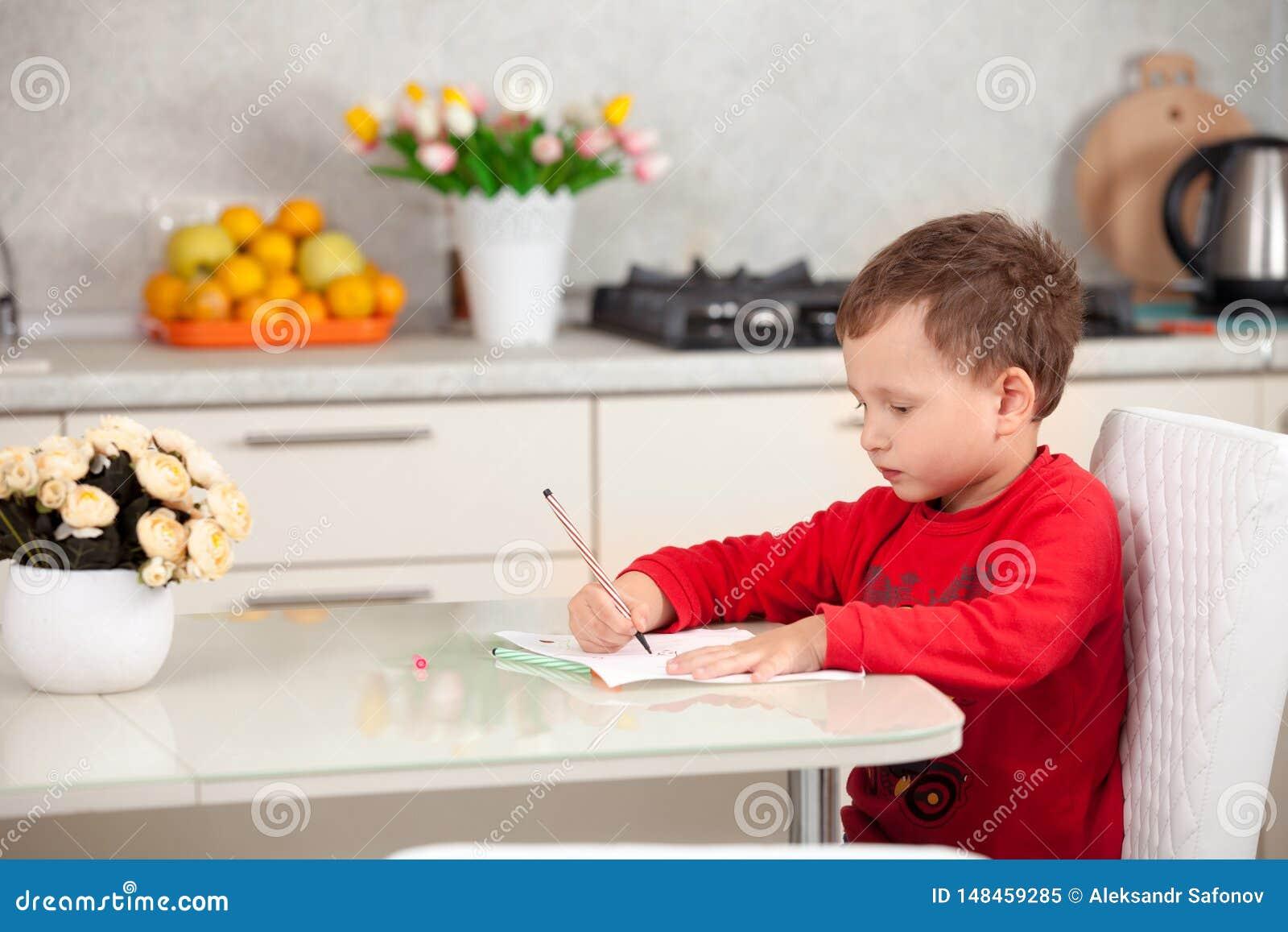 Inspirado por el muchacho dibuja una imagen en el papel en la tabla