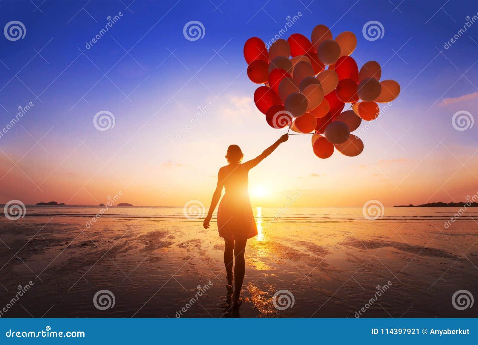 Inspiratie, vreugde en gelukconcept, silhouet van vrouw met vele vliegende ballons